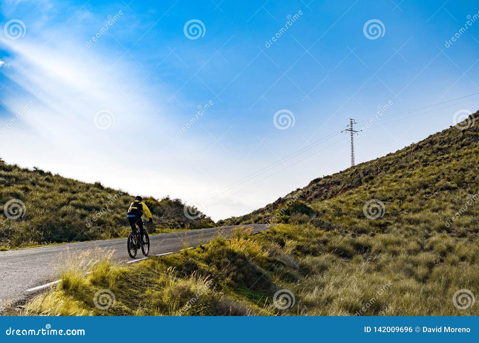 Montar a caballo femenino del ciclista de la bici de montaña ascendente a lo largo del camino de la montaña en España