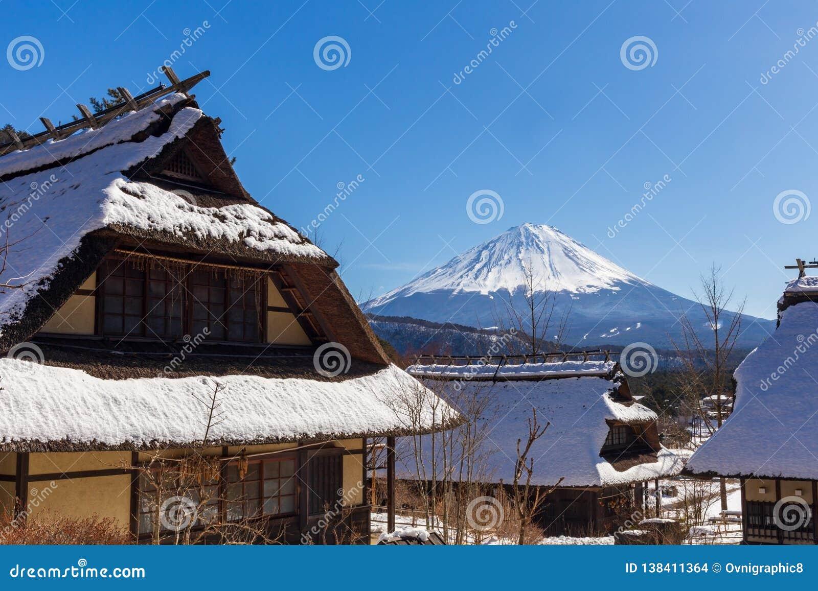 Monte Fuji em um dia de inverno claro, sobre casas cobridas com sapê japonesas tradicionais na vila tradicional de Iyashino-Sato