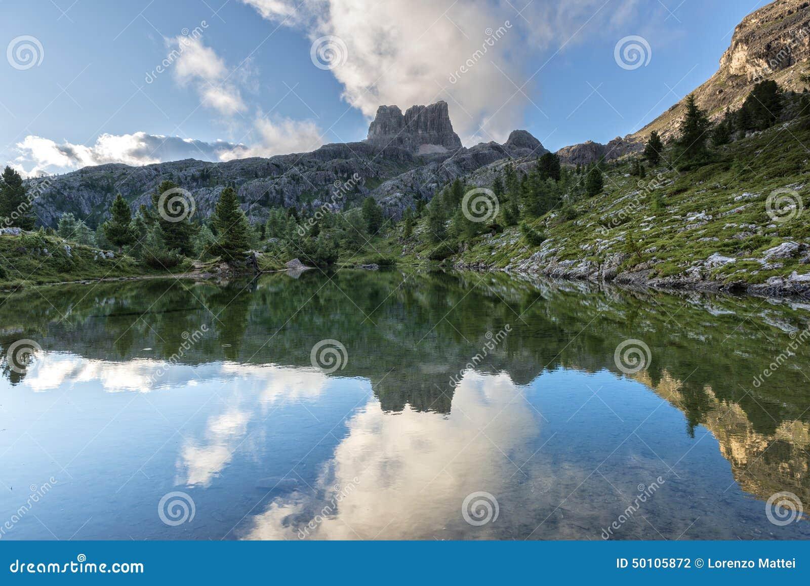 Montera Averau reflekterad i sjön Limedes på soluppgång, blå himmel med moln, Dolomites, Veneto, Italien