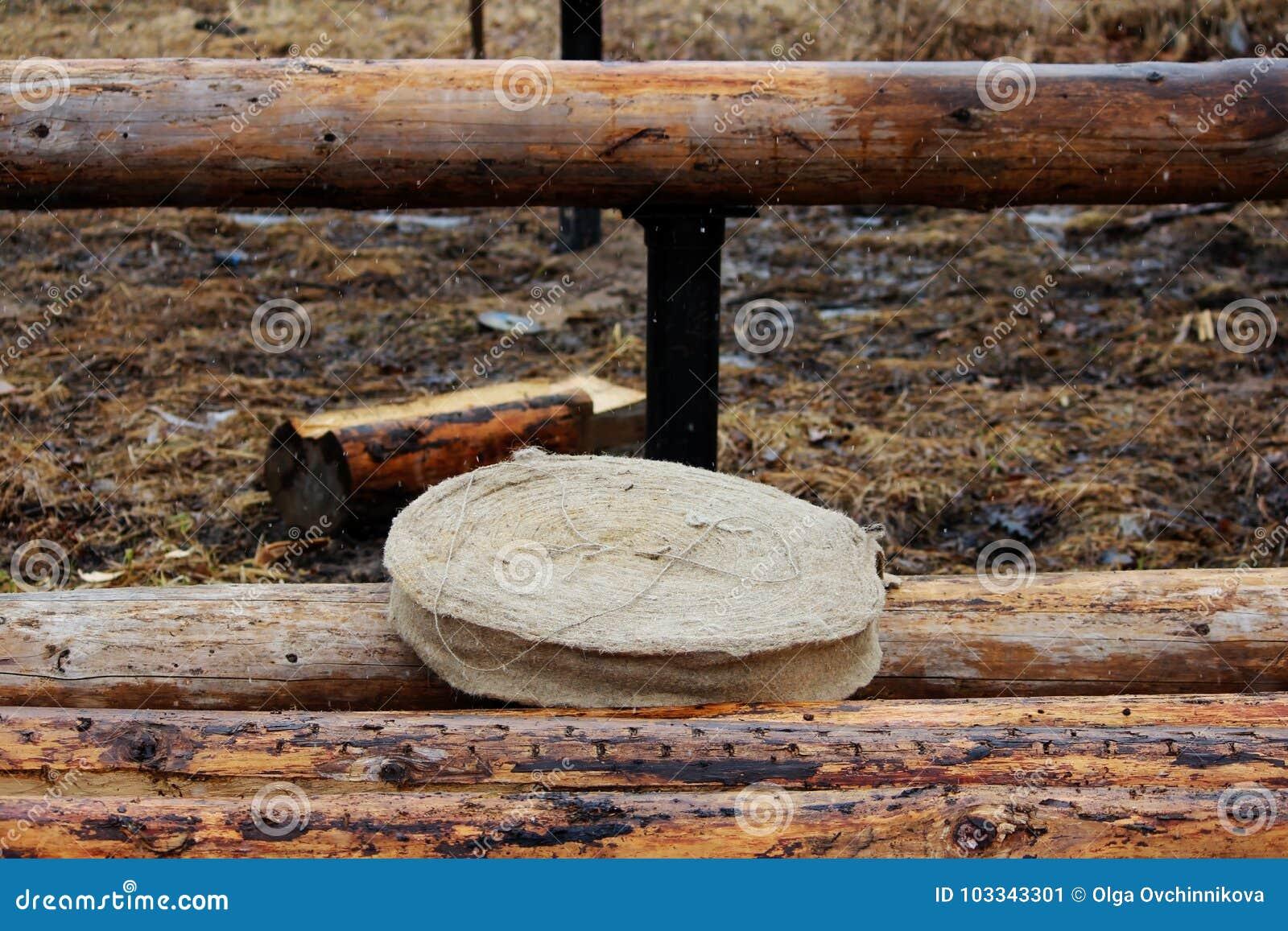 Montera en träram och byggande av ett hus Ryssland Textur av gamla träjournaler, interventureisoleringsjute och