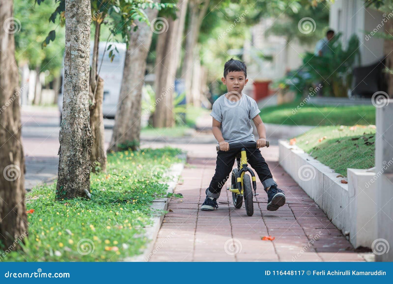 Montez un vélo utilisant la bicyclette de poussée ou d équilibre