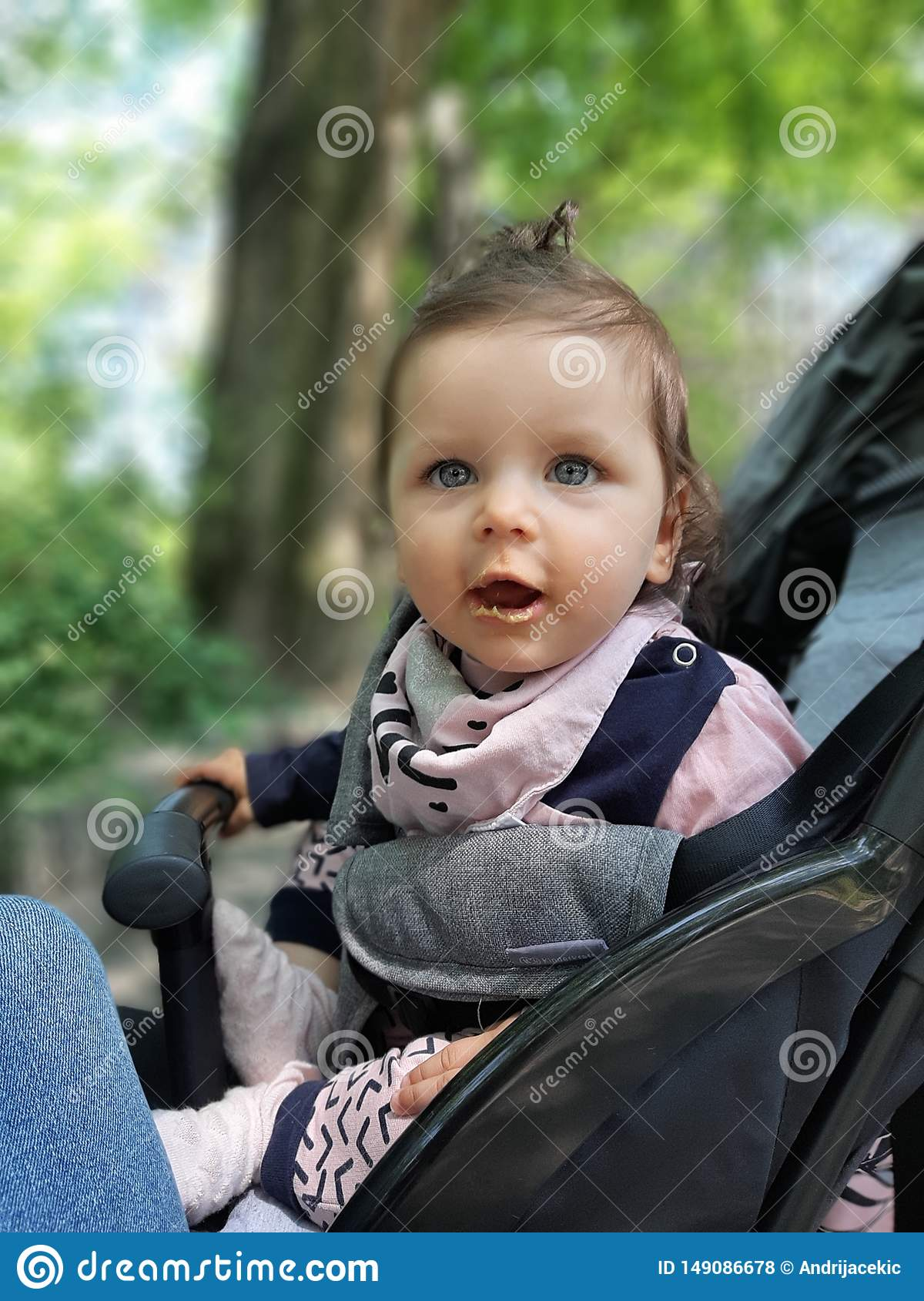 9 months old baby girl in the park eating
