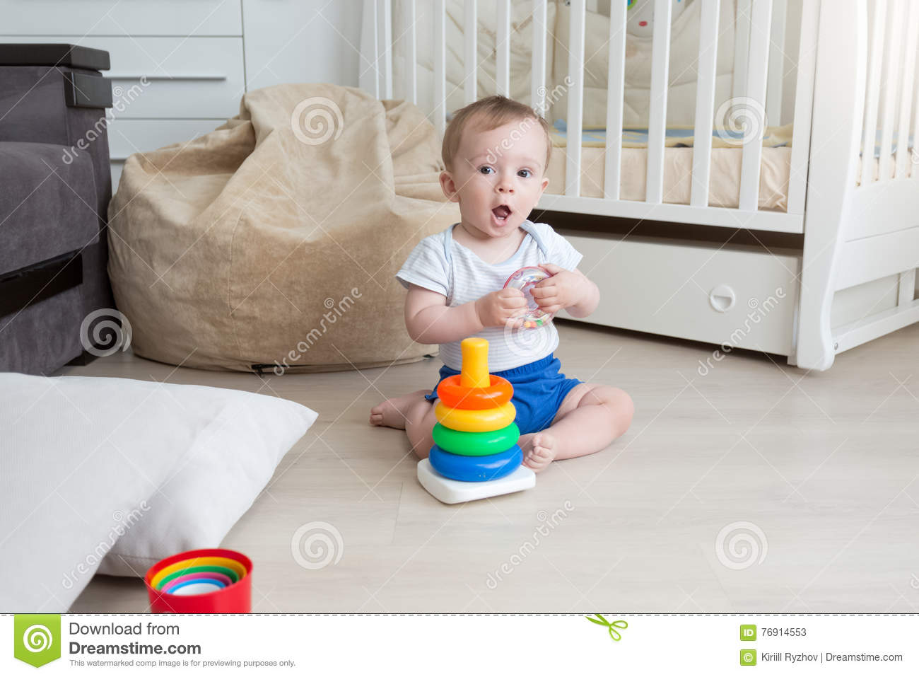 9 Months Old Baby Playing On Floor And Assembling Toy Tower Stock