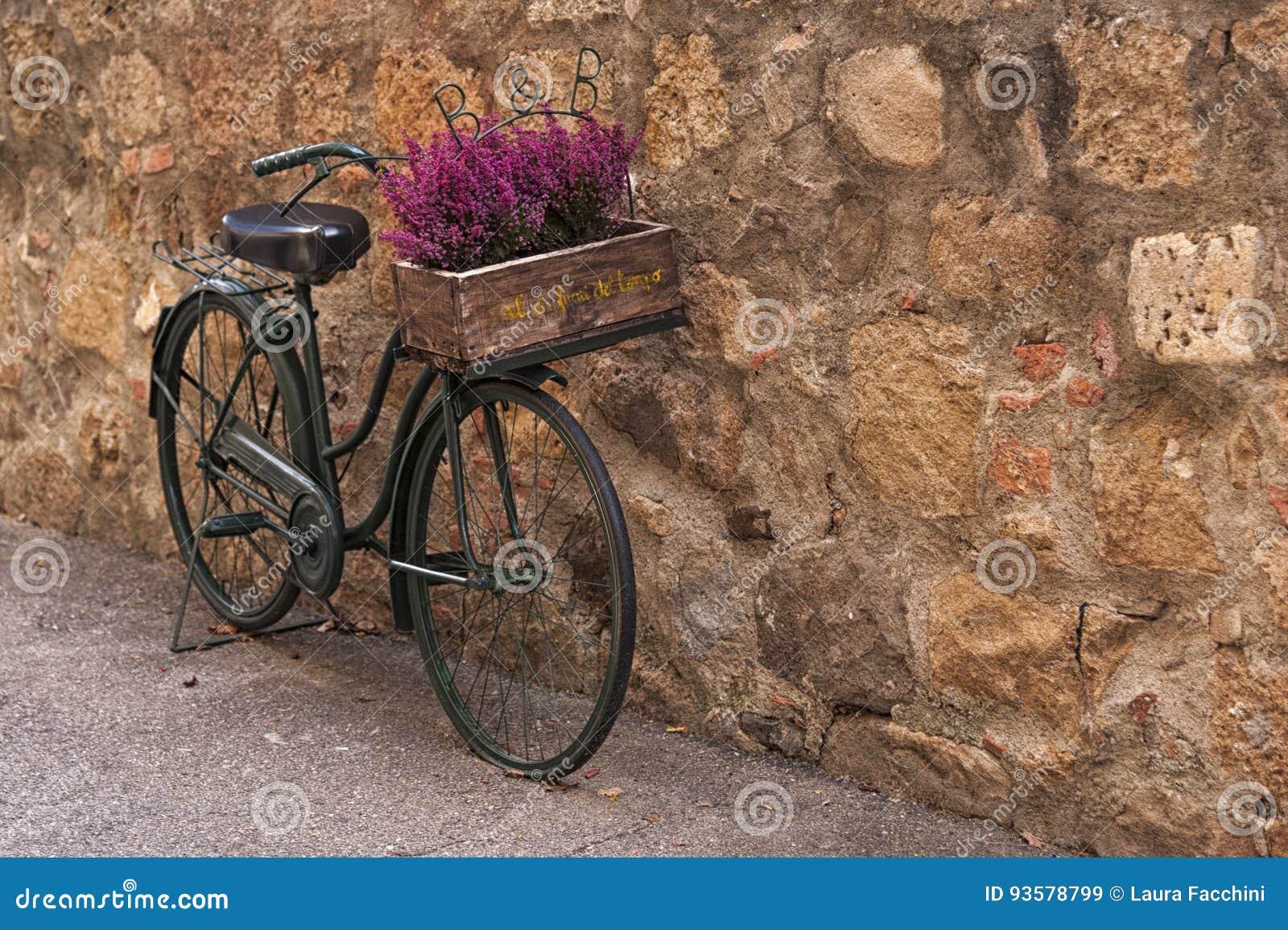 Montichiello - Italien, Oktober 29, 2016: En härlig cykel med blommor i en tyst gata i Montichiello, Tuscany