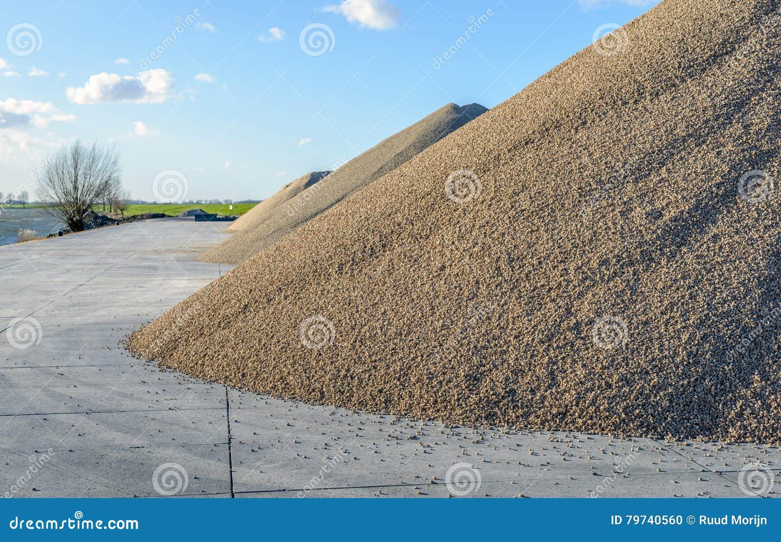 Montones grandes de la arena y de la grava almacenadas en un piso concreto