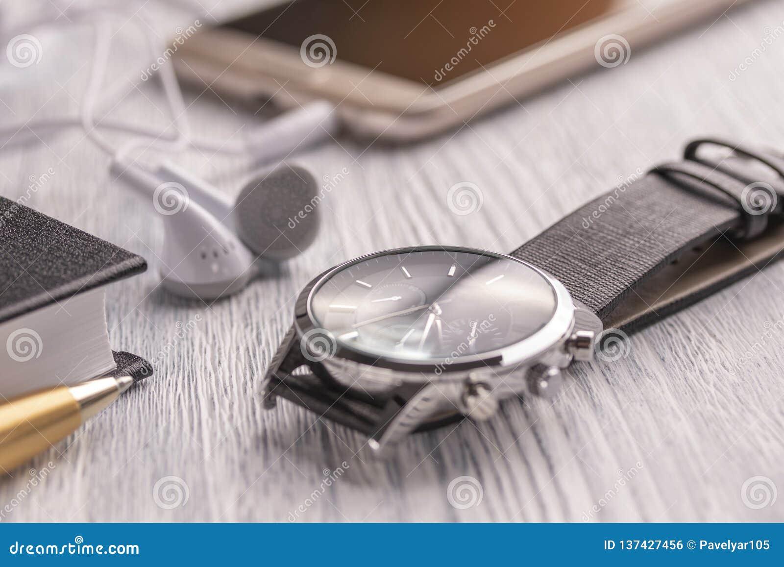 Montre-bracelet, téléphone portable avec des écouteurs et un carnet avec un stylo sur un vieux bureau et café blancs de bureau