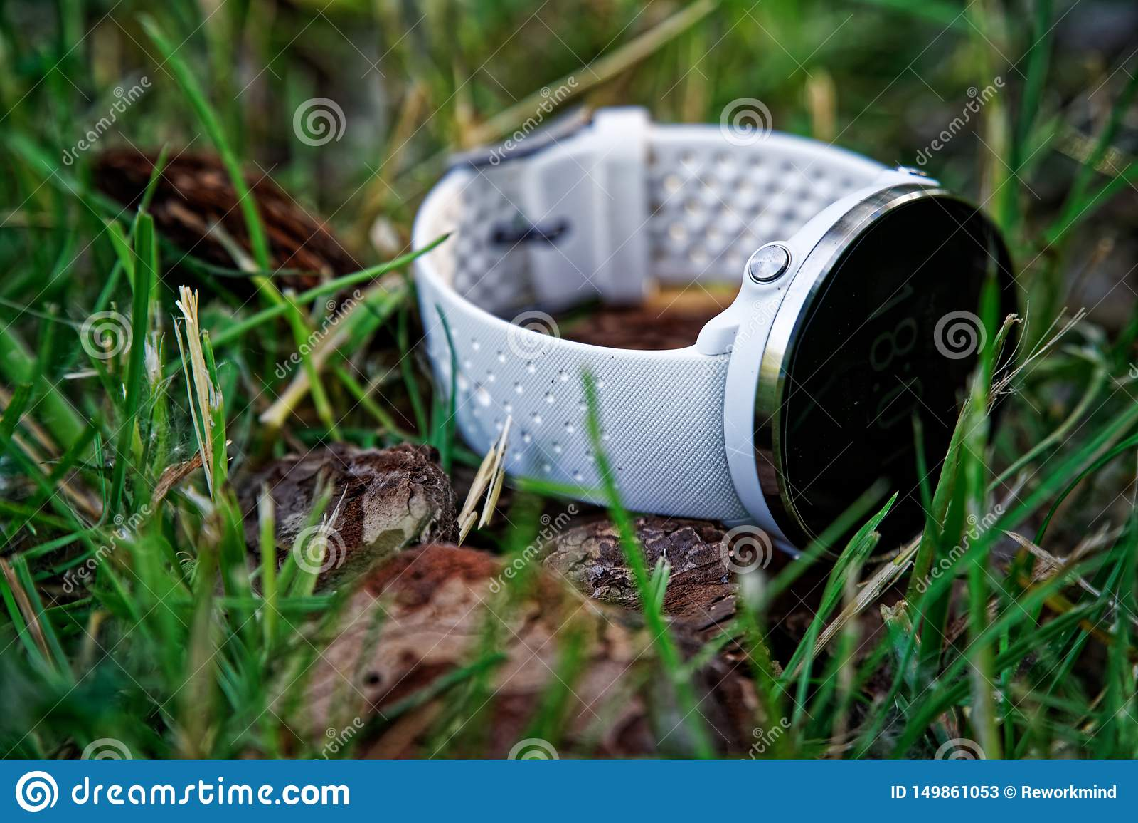 Montre de sport pour la couleur blanche fonctionnante au sol dans l herbe Montre de forme physique pour la formation quotidienne