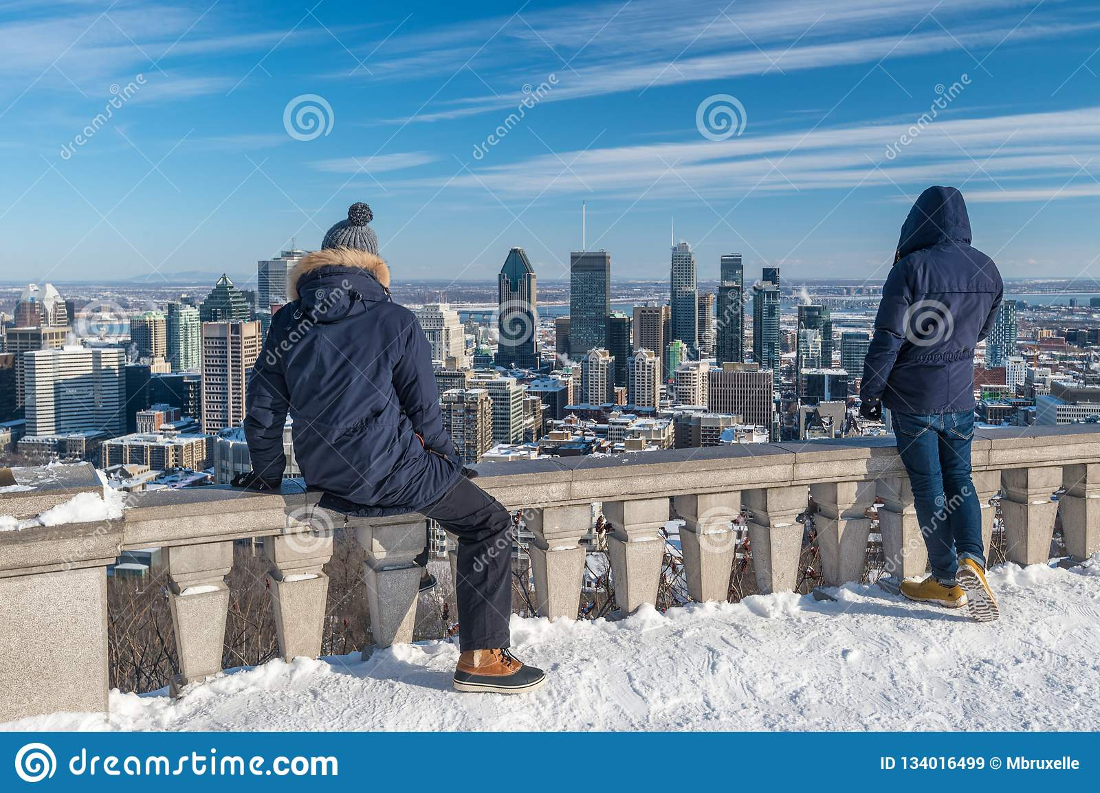 Tourists looking at Montreal Skyline from Kondiaronk belvedere in winter