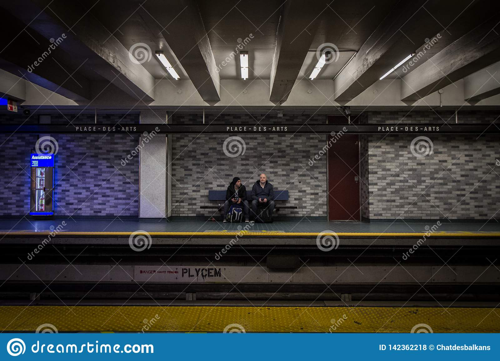 People waiting for a subway in place des Arts station platform, green line, sitting on a bench.