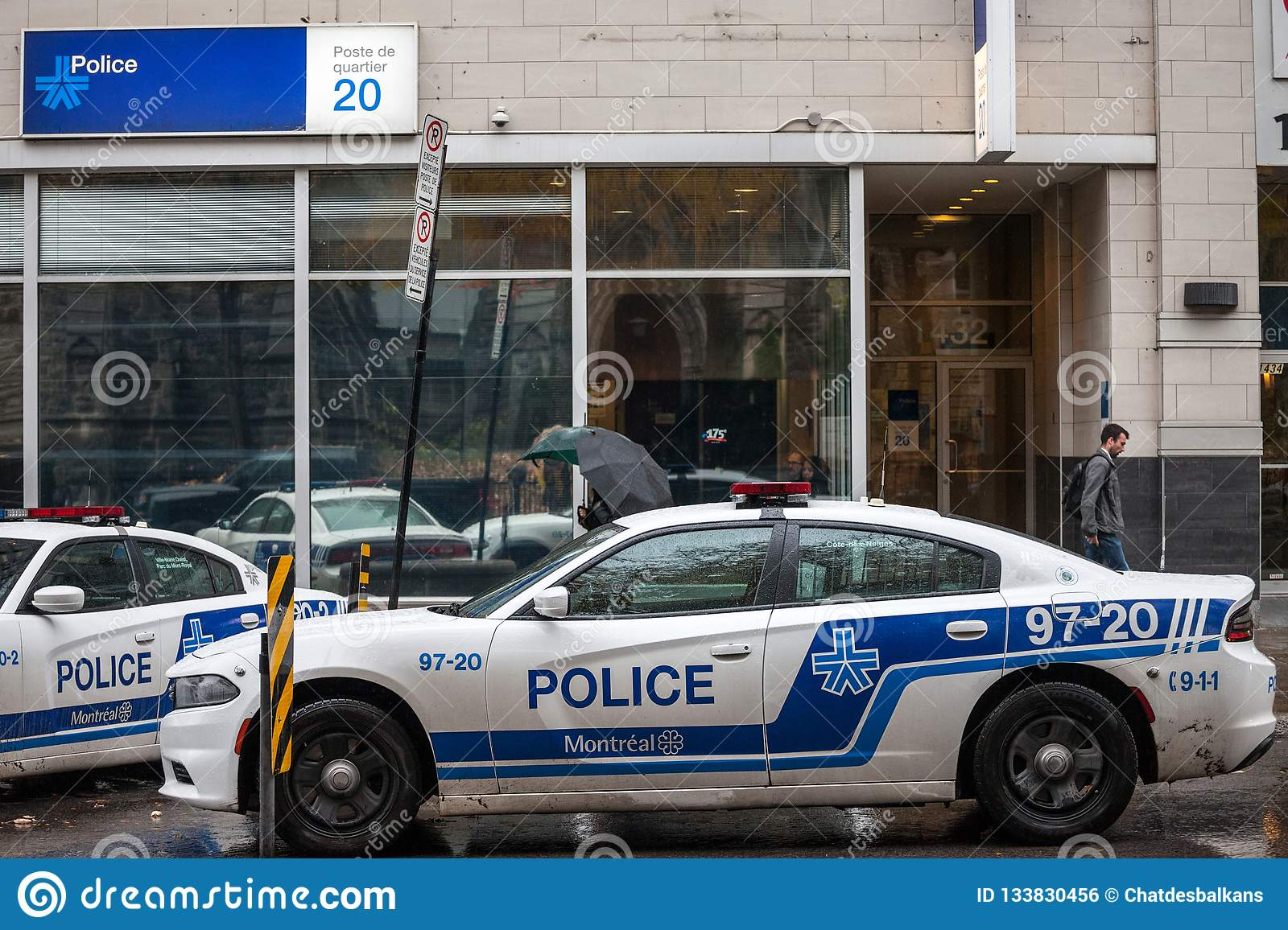 Two Montreal Police Service SPVM cars standing in front of a local police station. The SPVM is the police of Montreal, Quebec