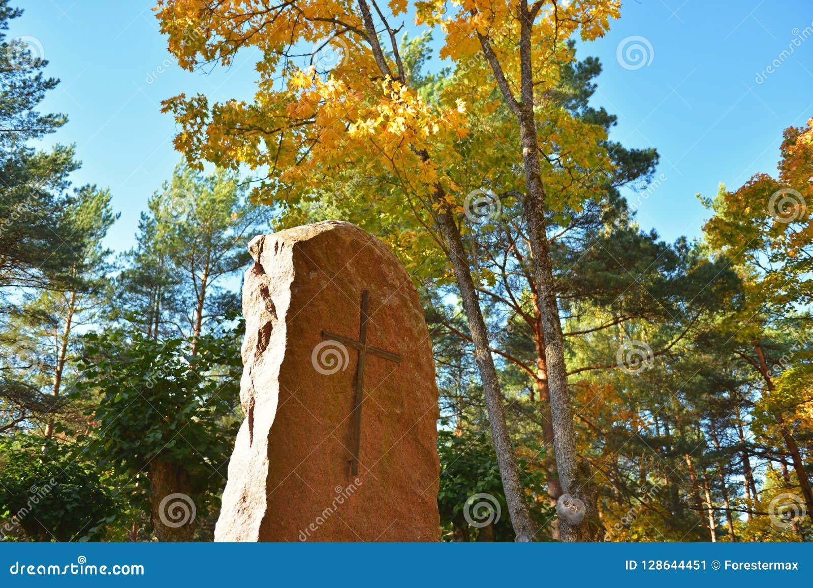 Monumento di pietra con un incrocio nel parco di autunno al monastero