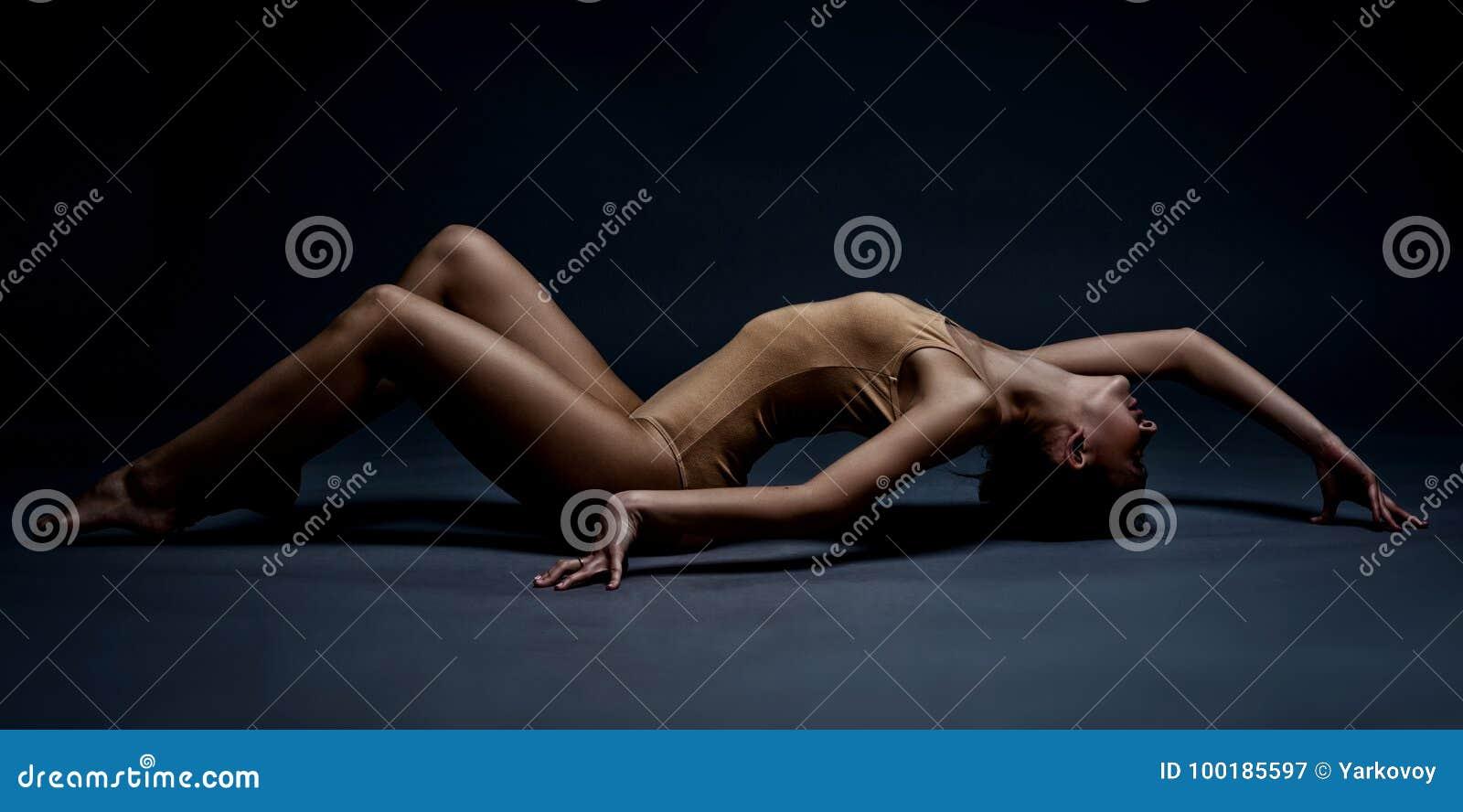 Mooi atletisch meisje op de vloer Studioportret in motie