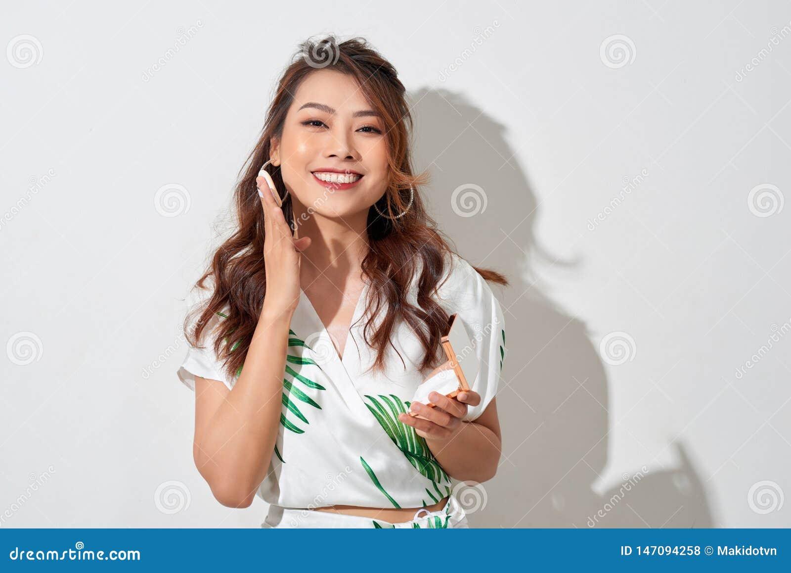 Mooi Aziatisch meisje in de zomerkleding die samenstelling met haar klein spiegel en poeder in zonnige middag doen