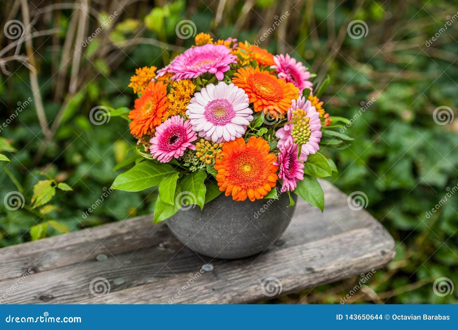 Mooi bloemboeket in bloempot op houten bank