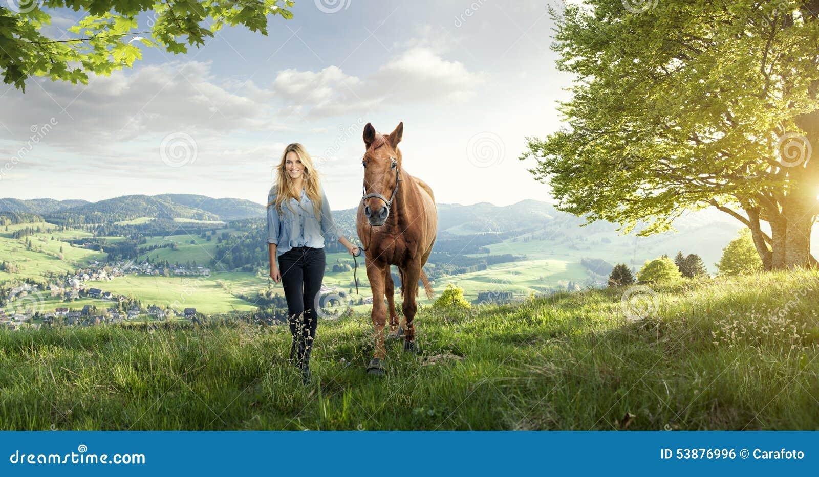Mooi blond meisje met een paard in prachtige landschappen
