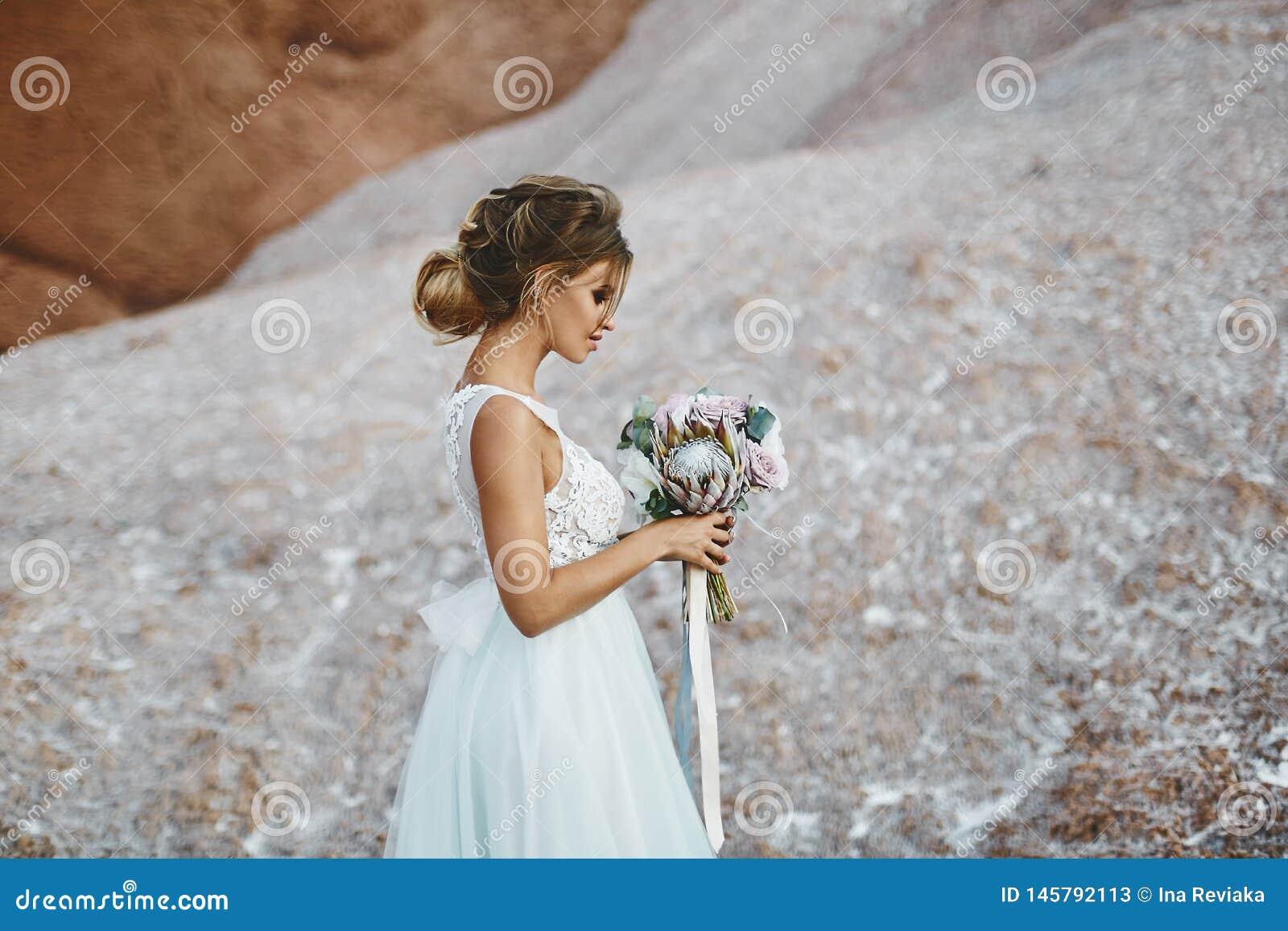 Mooi blonde modelmeisje met de modellering van huwelijkskapsel in een modieuze witte kantkleding met een boeket van exotics