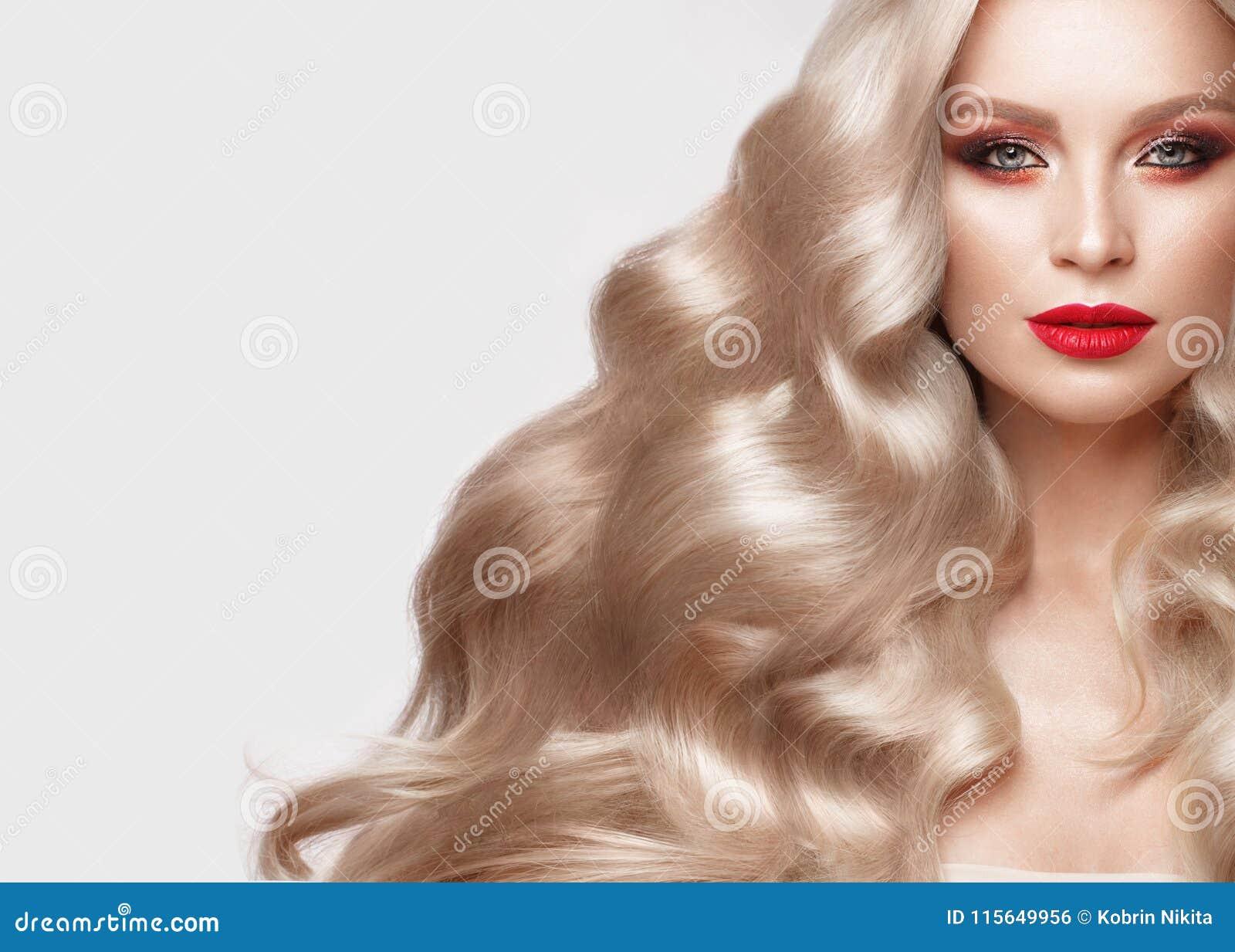 Mooi blonde op een Hollywood-manier met krullen, natuurlijke make-up en rode lippen Het gezicht en het haar van de schoonheid