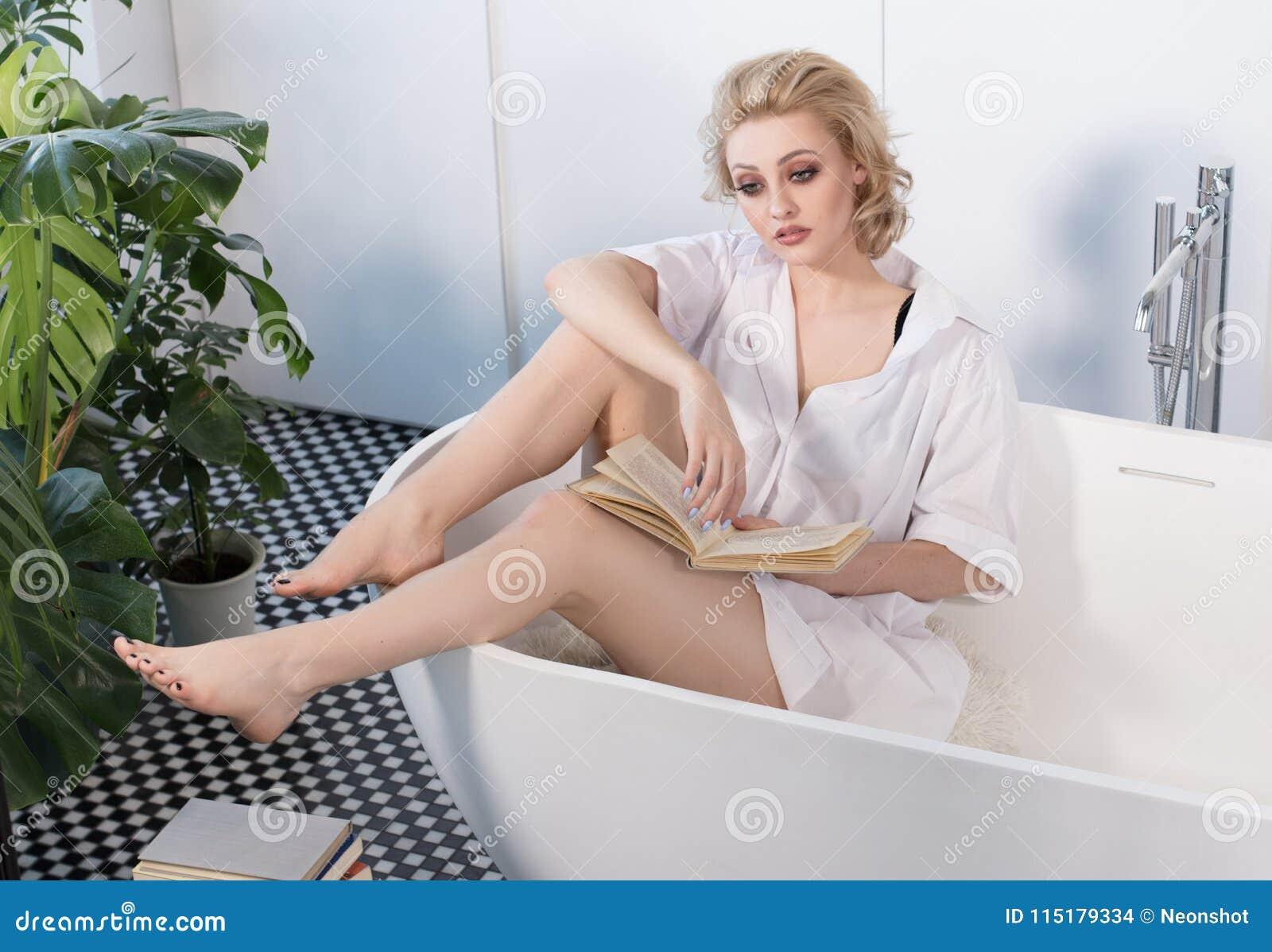 Mooi blondemeisje die een boek in badkamers lezen