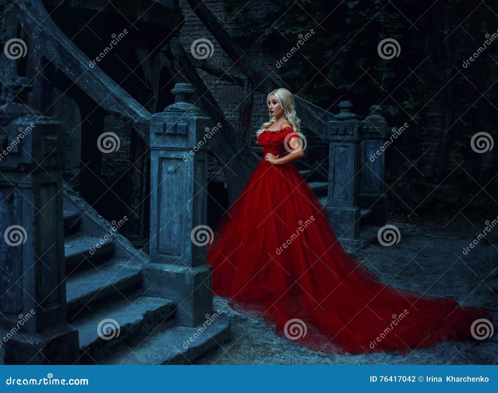 Mooi blondemeisje in een luxueuze rode kleding