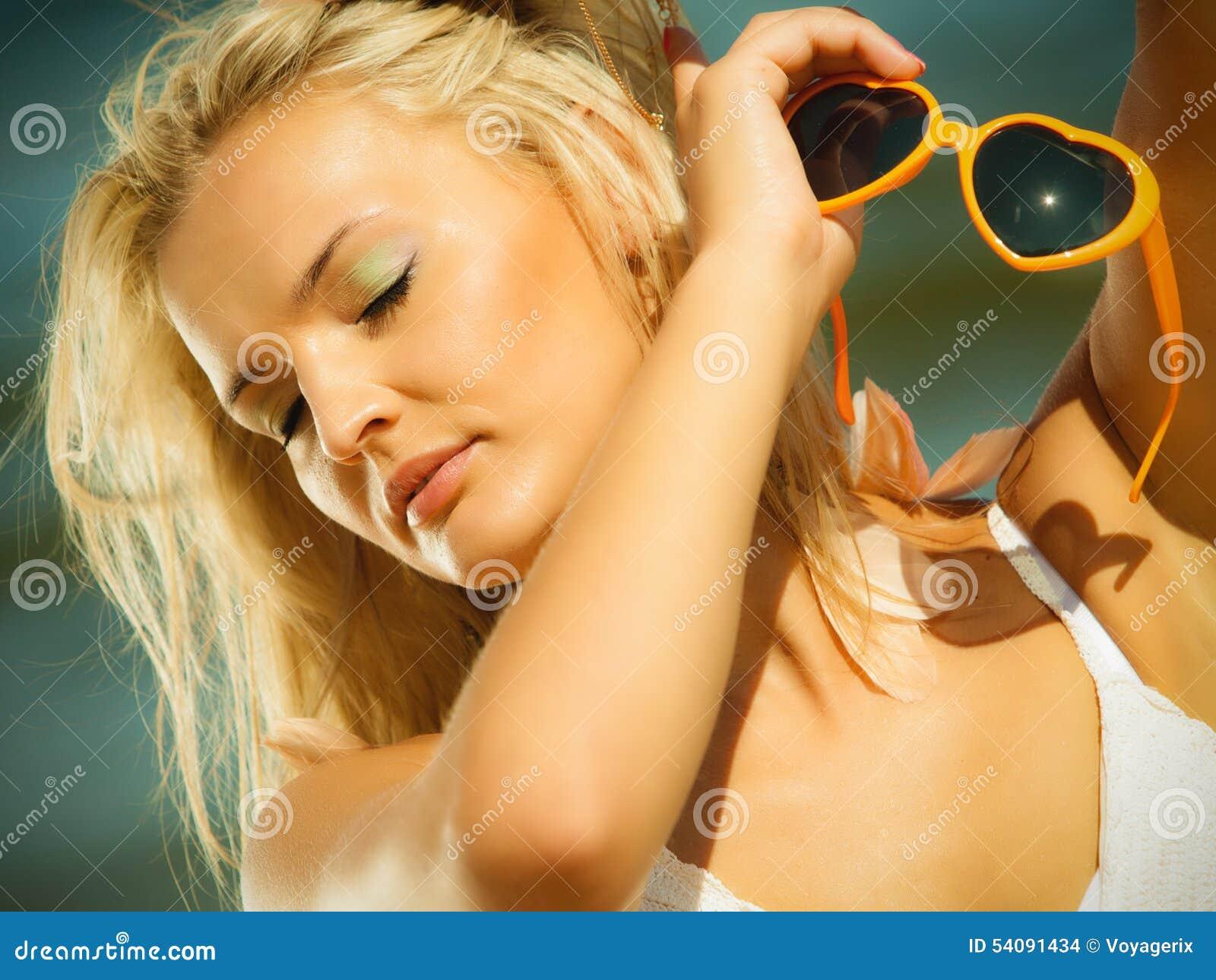 Mooi blondemeisje in zonnebril openlucht