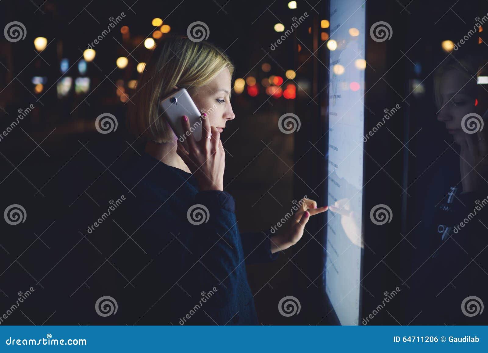 Mooi blondewijfje die op mobiele telefoon spreken terwijl wat betreft het grote digitale scherm dat het wijzen van op licht,