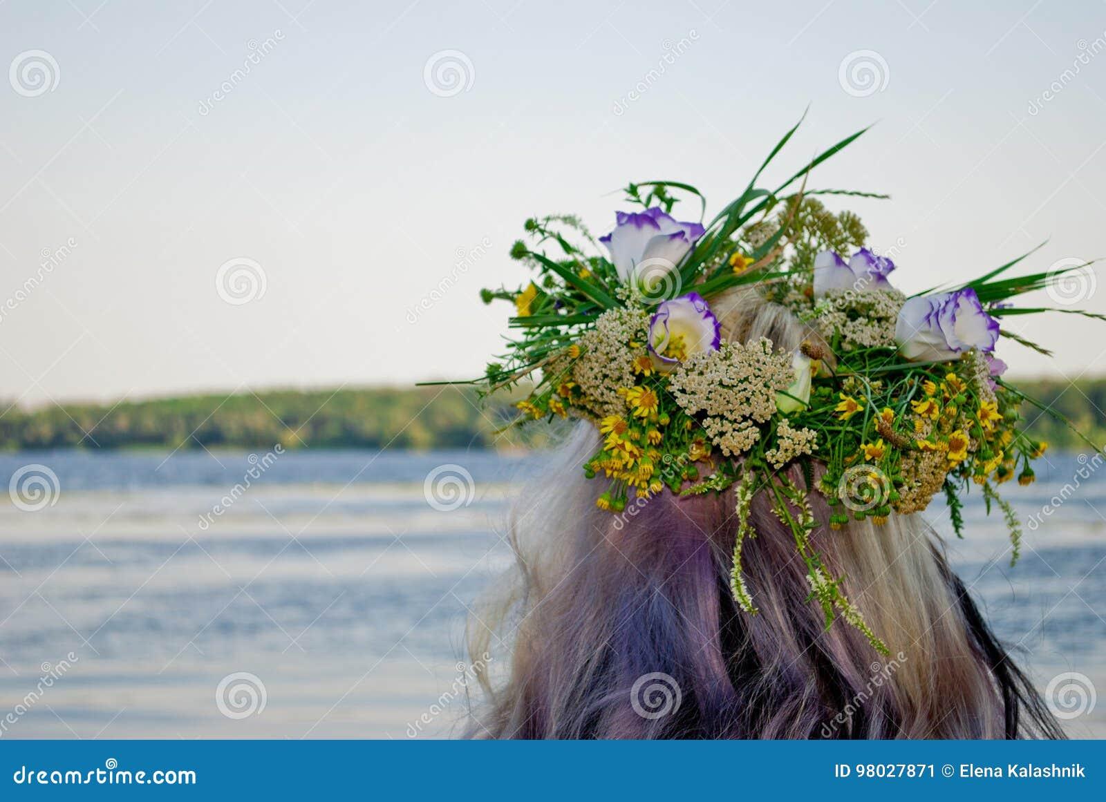 Mooi boeket van kroon van wilde bloemen op het hoofd van een meisje dichtbij de waterrivier