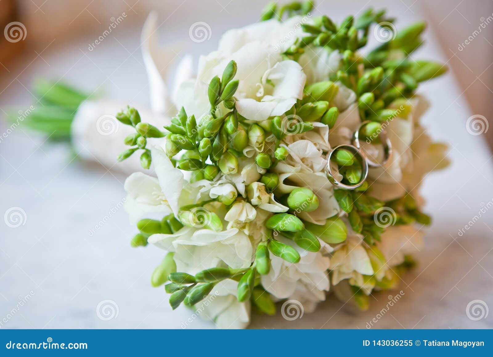 Mooi bruids boeket met witte fresia en trouwringen Horizontale richtlijn close-up Concept gelukkige huwelijksdag