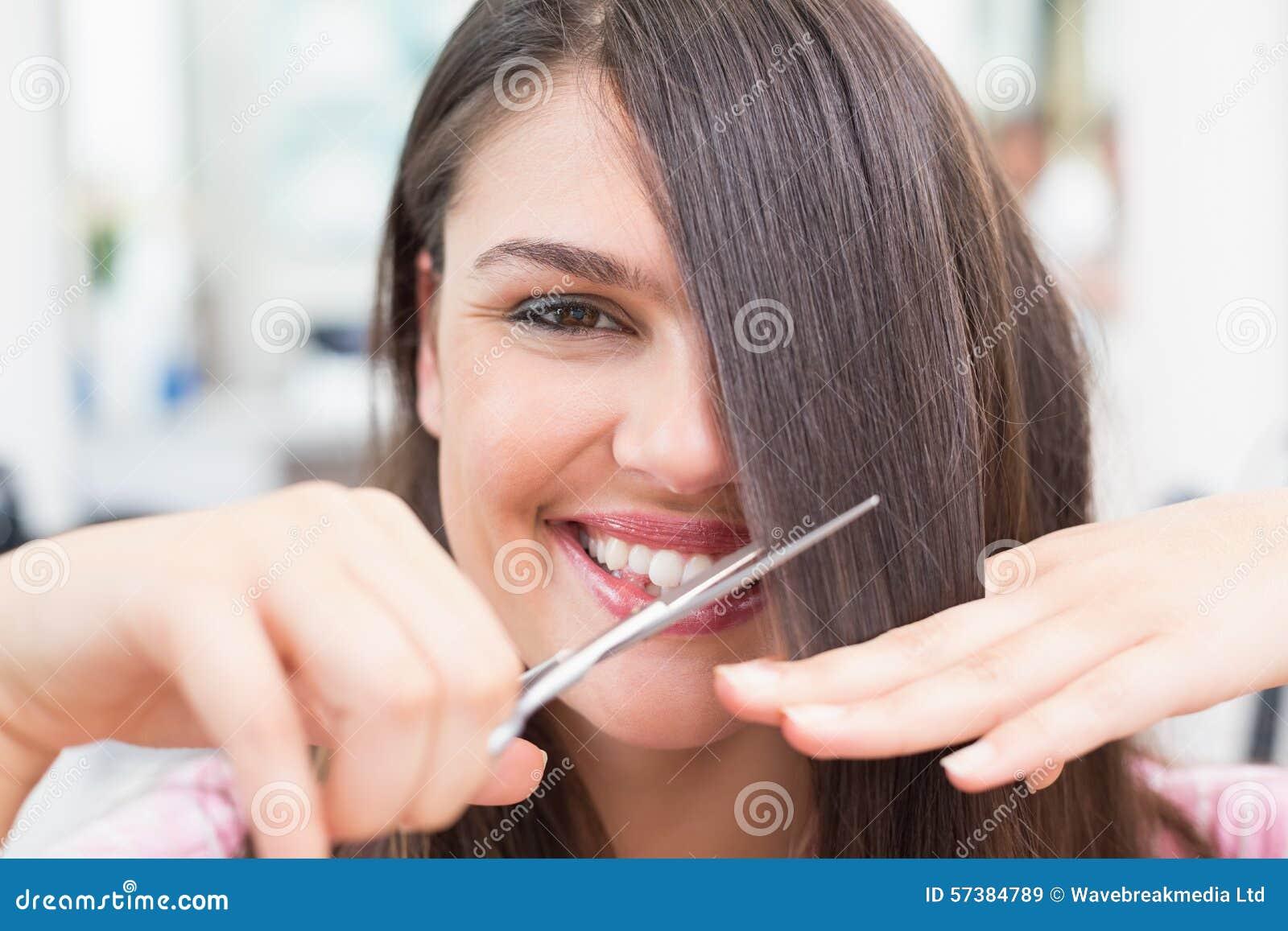 Mooi brunette die haar haarbesnoeiing krijgen