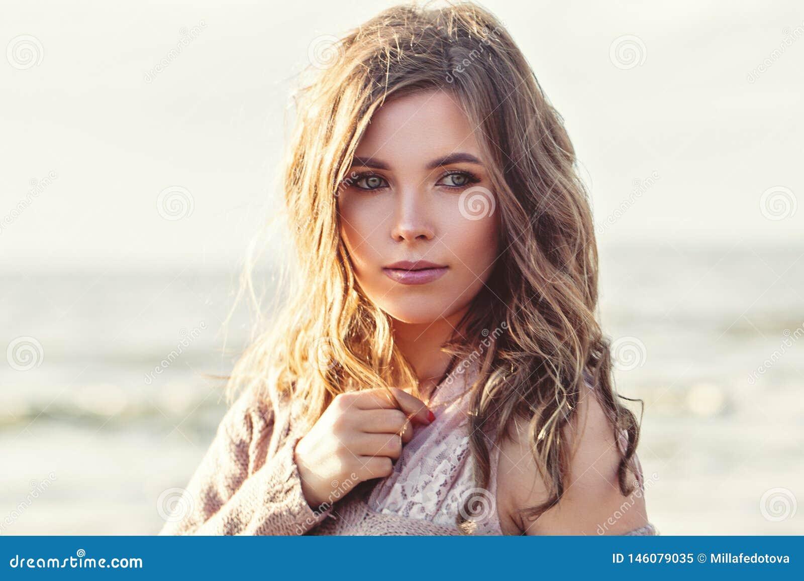Mooi de close-upportret van het vrouwengezicht Mooi meisje met lang krullend bruin haar op oceaanachtergrond Perfecte Natuurlijke