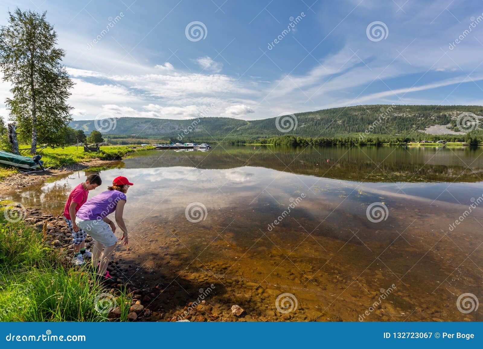 Mooi de zomerlandschap van een bergmeer met boten Een jonge jongen en een vrouw in de voorgrond