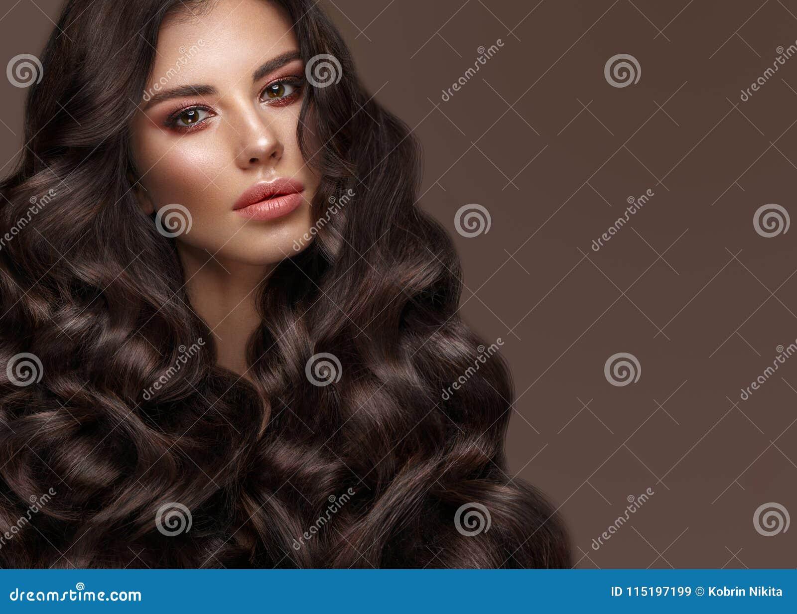 Mooi donkerbruin model: krullen, klassieke make-up en volledige lippen Het schoonheidsgezicht