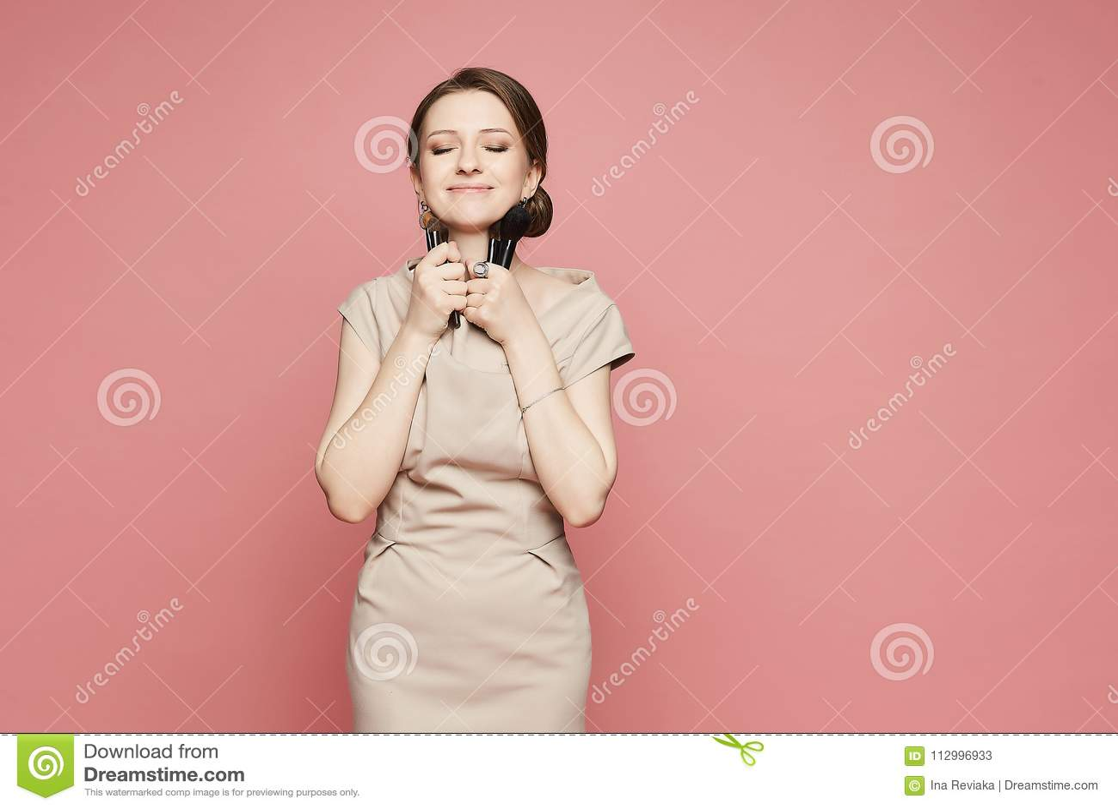 Mooi en modieus donkerbruin modelmeisje, in beige kleding, dwazen rond met een make-upborstel