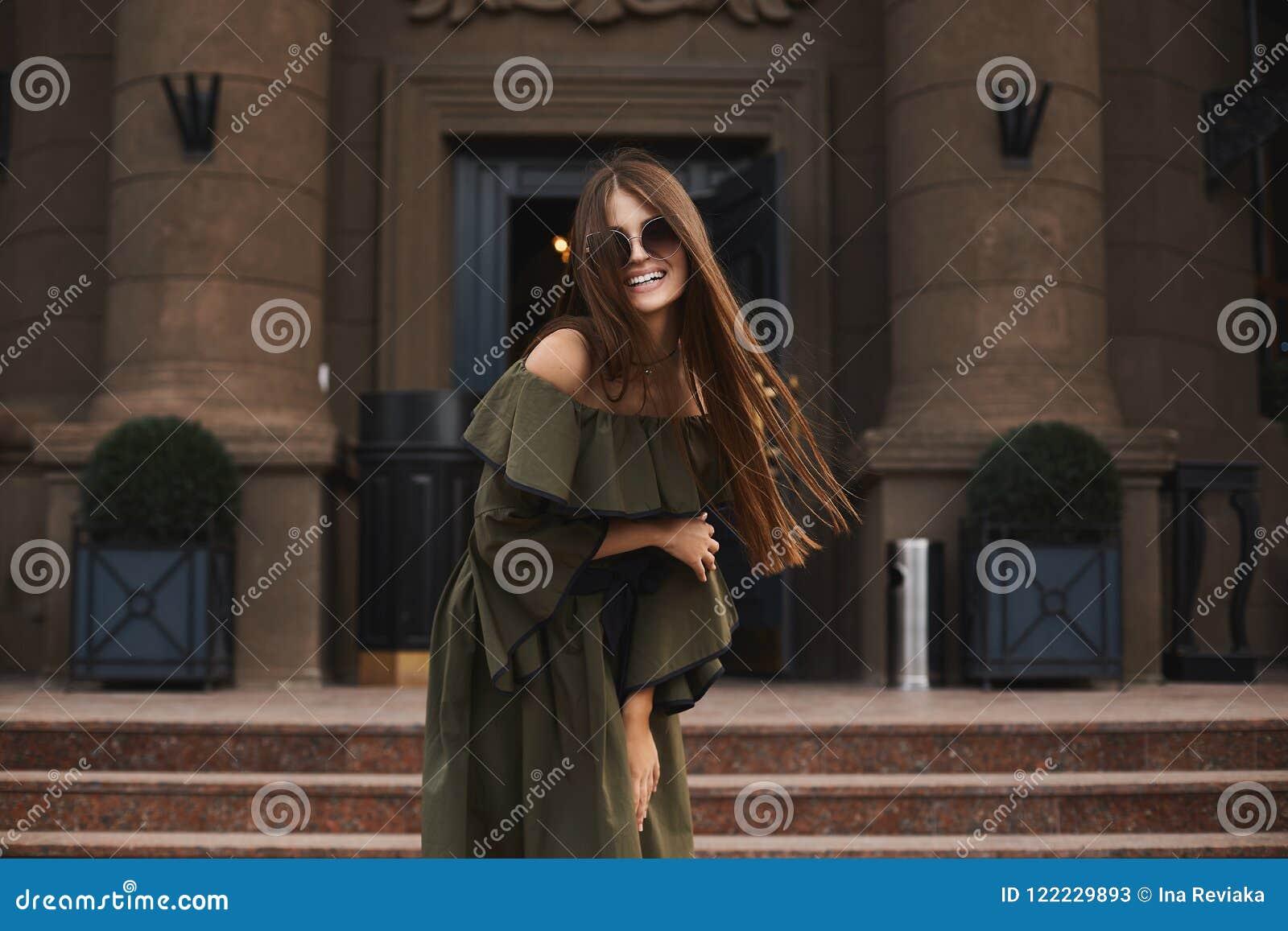 Mooi en modieus donkerbruin modelmeisje met charmante glimlach, in modieuze kleding met naakte schouders en in in sunglas
