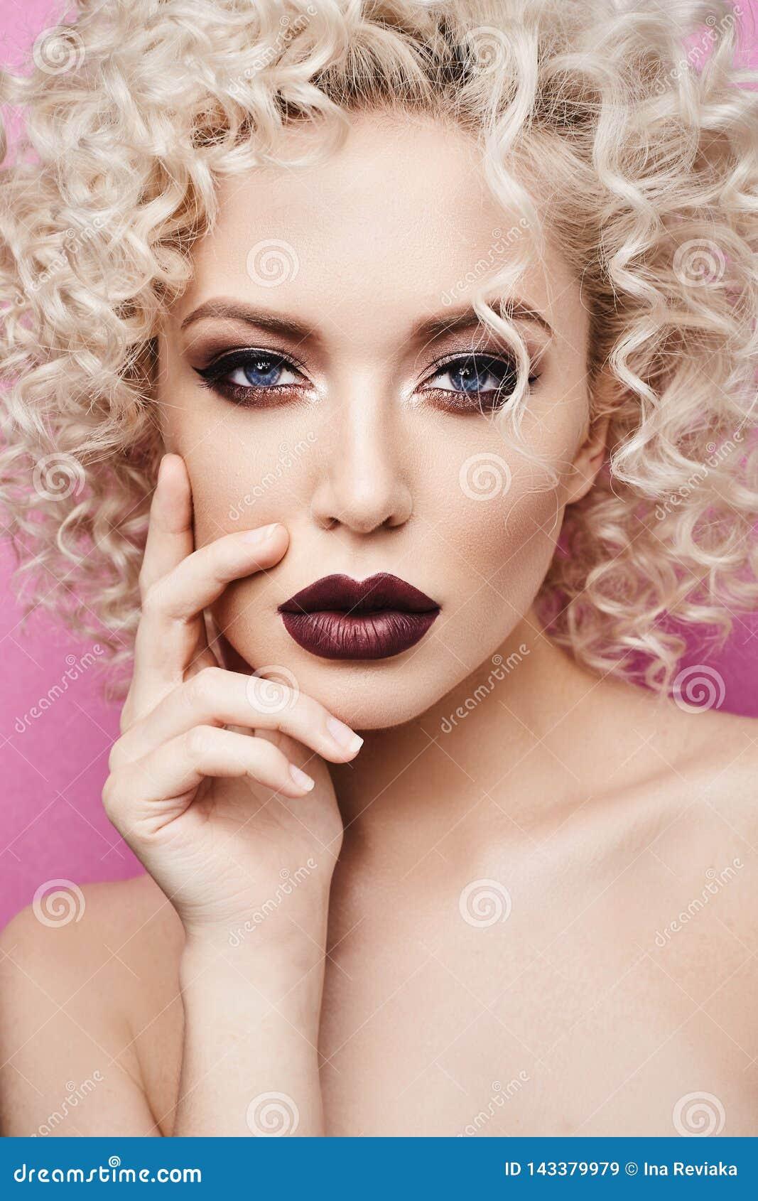 Mooi en modieus modelmeisje met verbazende blauwe ogen, met krullend blondehaar en met donkerrode die lippen worden geïsoleerd bi