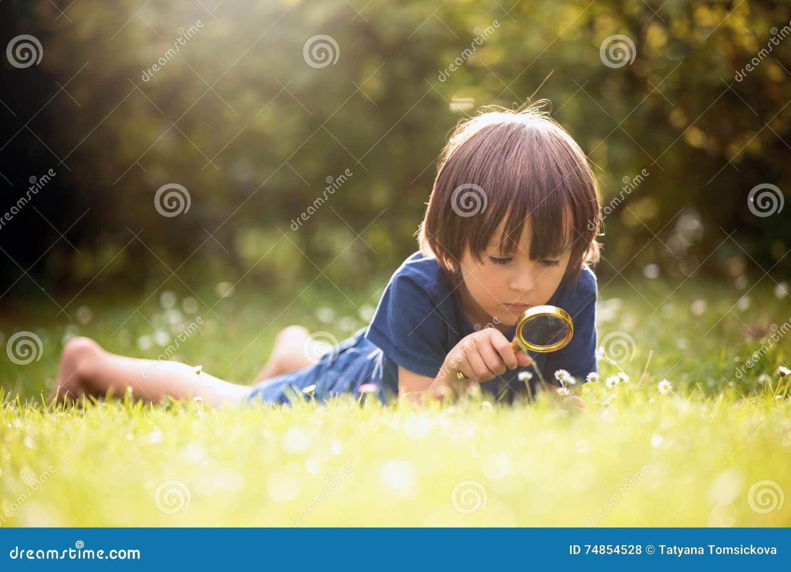 Mooi gelukkig kind, jongen, die aard met het overdrijven gla onderzoeken