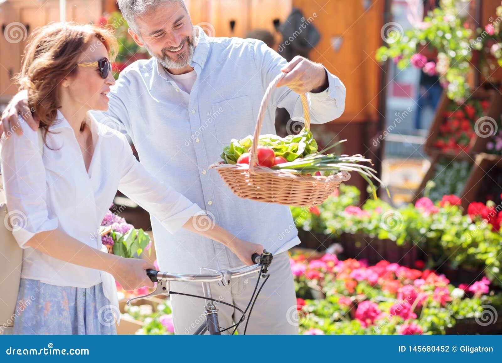 Mooi gelukkig medio volwassen paar die van kruidenierswinkel het winkelen terugkeren
