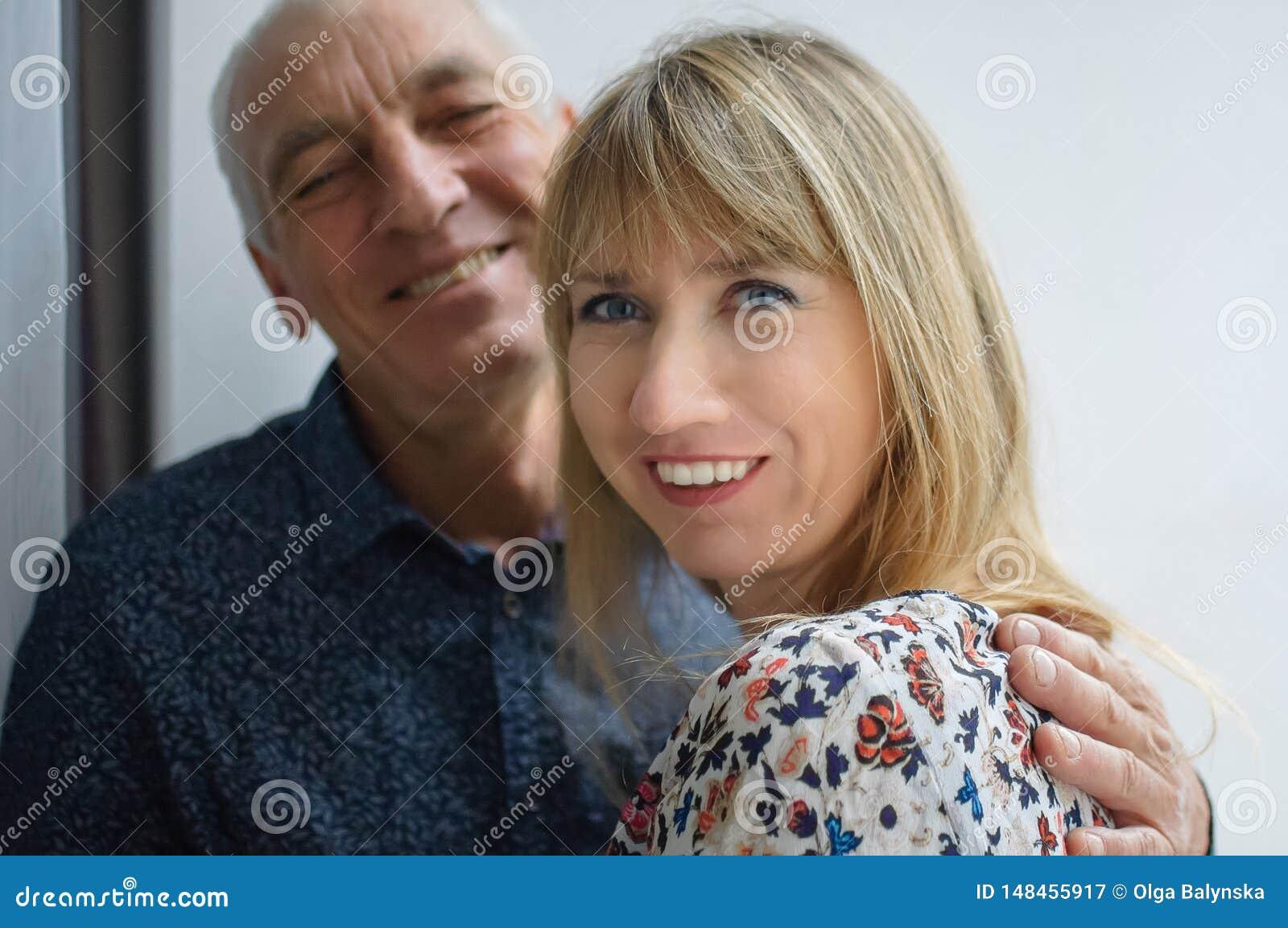 Mooi gelukkig portret van bejaarde die zijn jonge blonde-haired glimlachende vrouw koesteren die warme kleding dragen Paar met Le