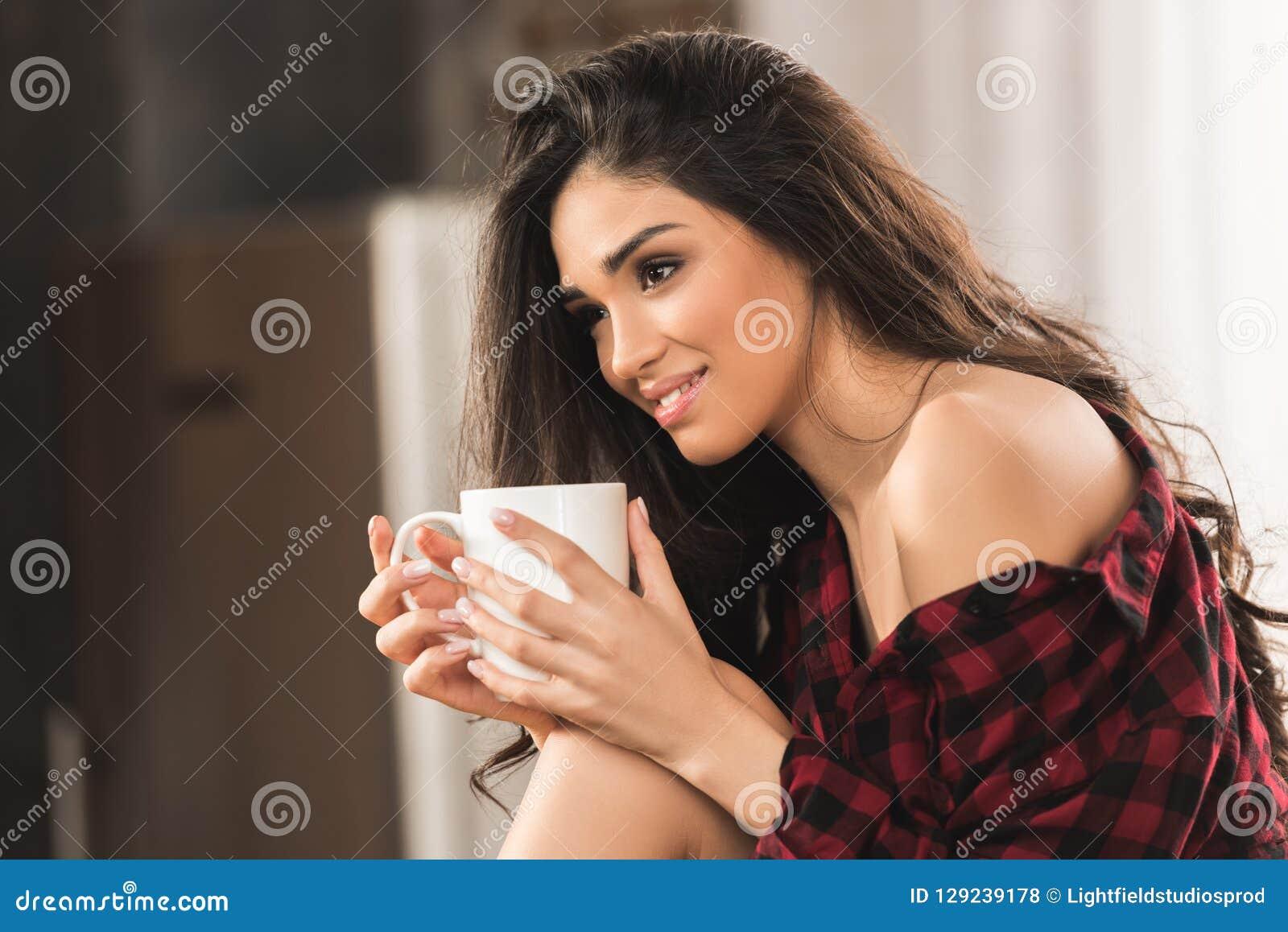 Mooi glimlachend meisje in de geruite kop van de overhemdsholding van koffie en weg het kijken