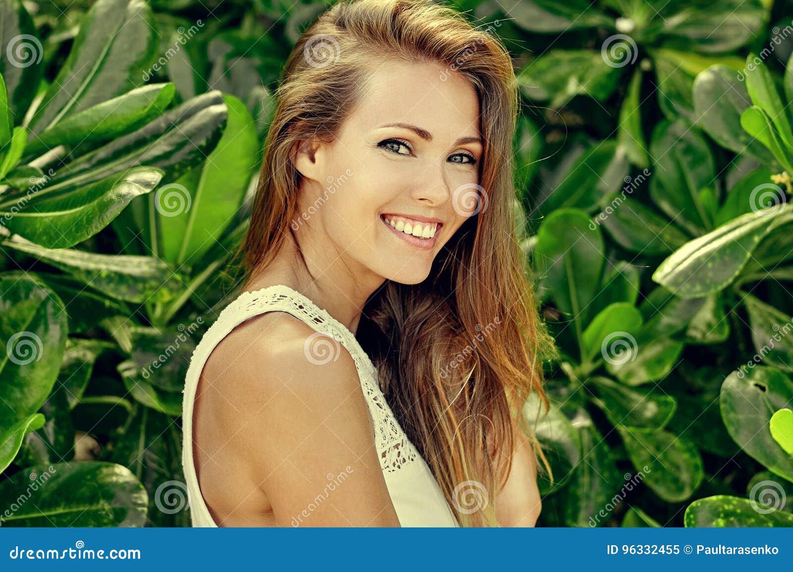 Mooi glimlachend meisje in groene tuin - sluit omhoog