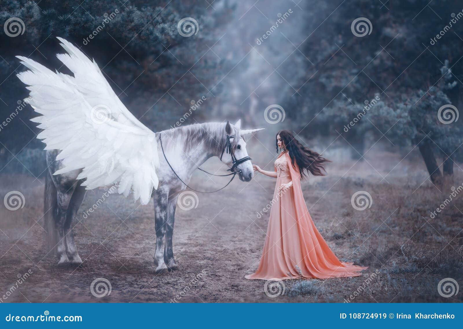 Mooi, jong elf, die met een eenhoorn in het bos lopen is zij gekleed in een lange oranje kleding met een mantel De mooie pluim
