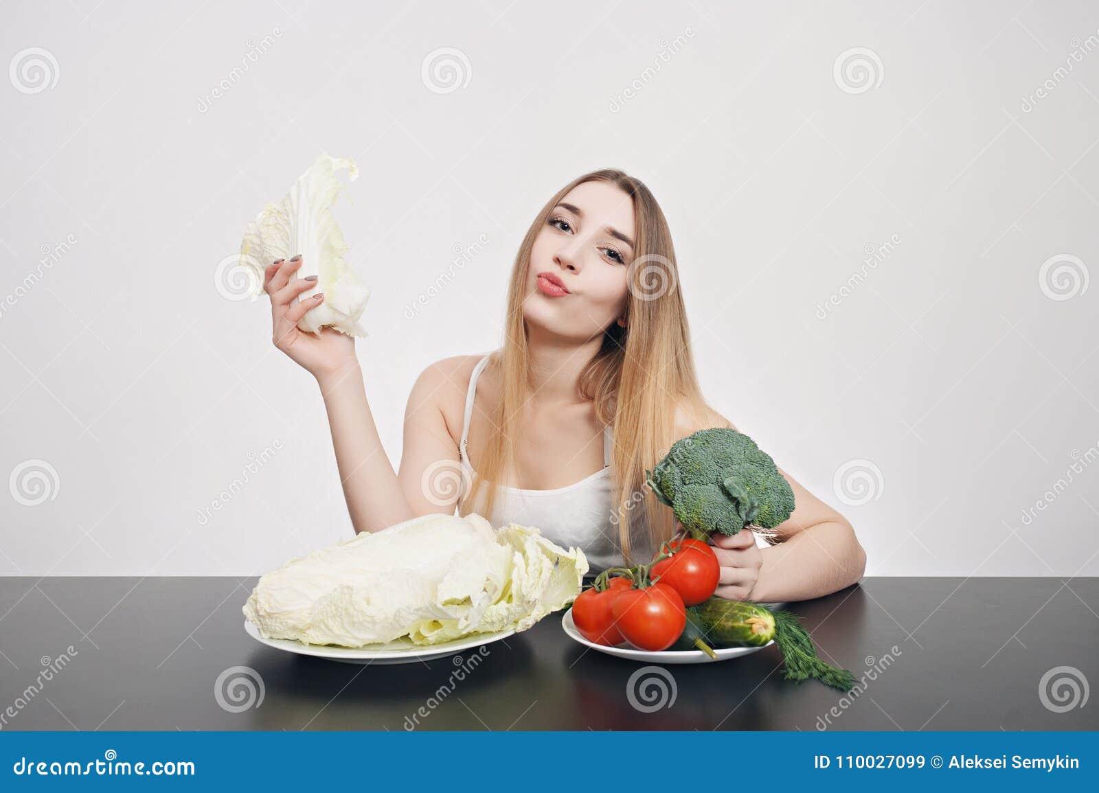 Mooi jong meisje bij een lijst met groenten voor salade Kok thuis Concept gezond, vegetarisch voedsel