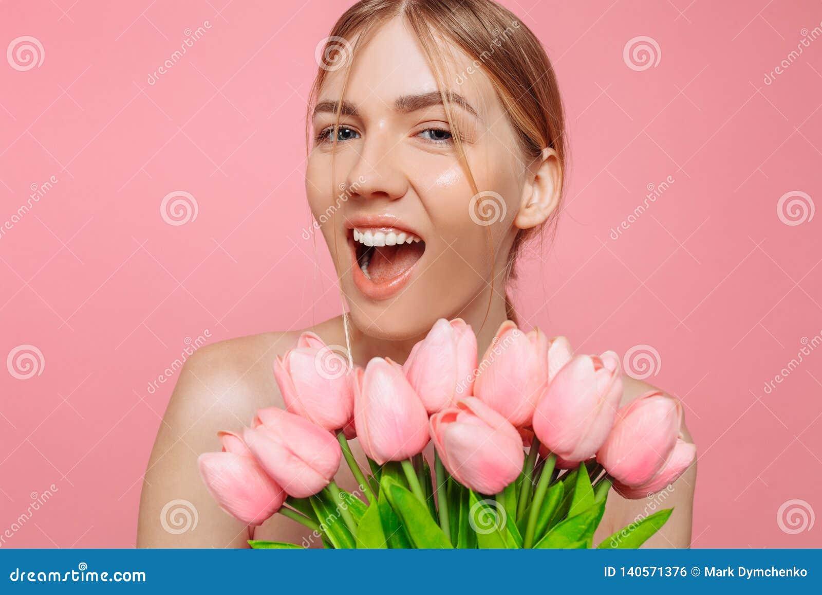 Mooi jong meisje die met schone huid een boeket van roze tulpen, op een roze achtergrond houden