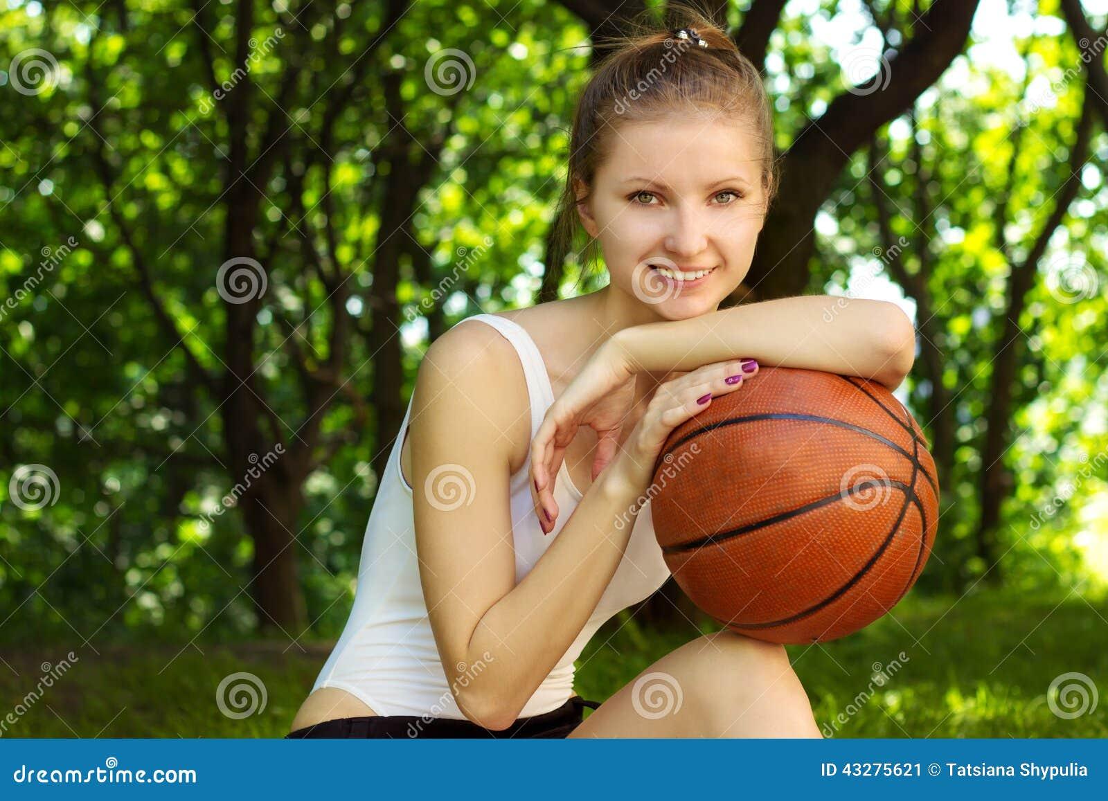 Mooi jong meisje met een glimlach die met een basketbalbal binnen zitten voor sporten stock - Kantoor voor een klein meisje ...