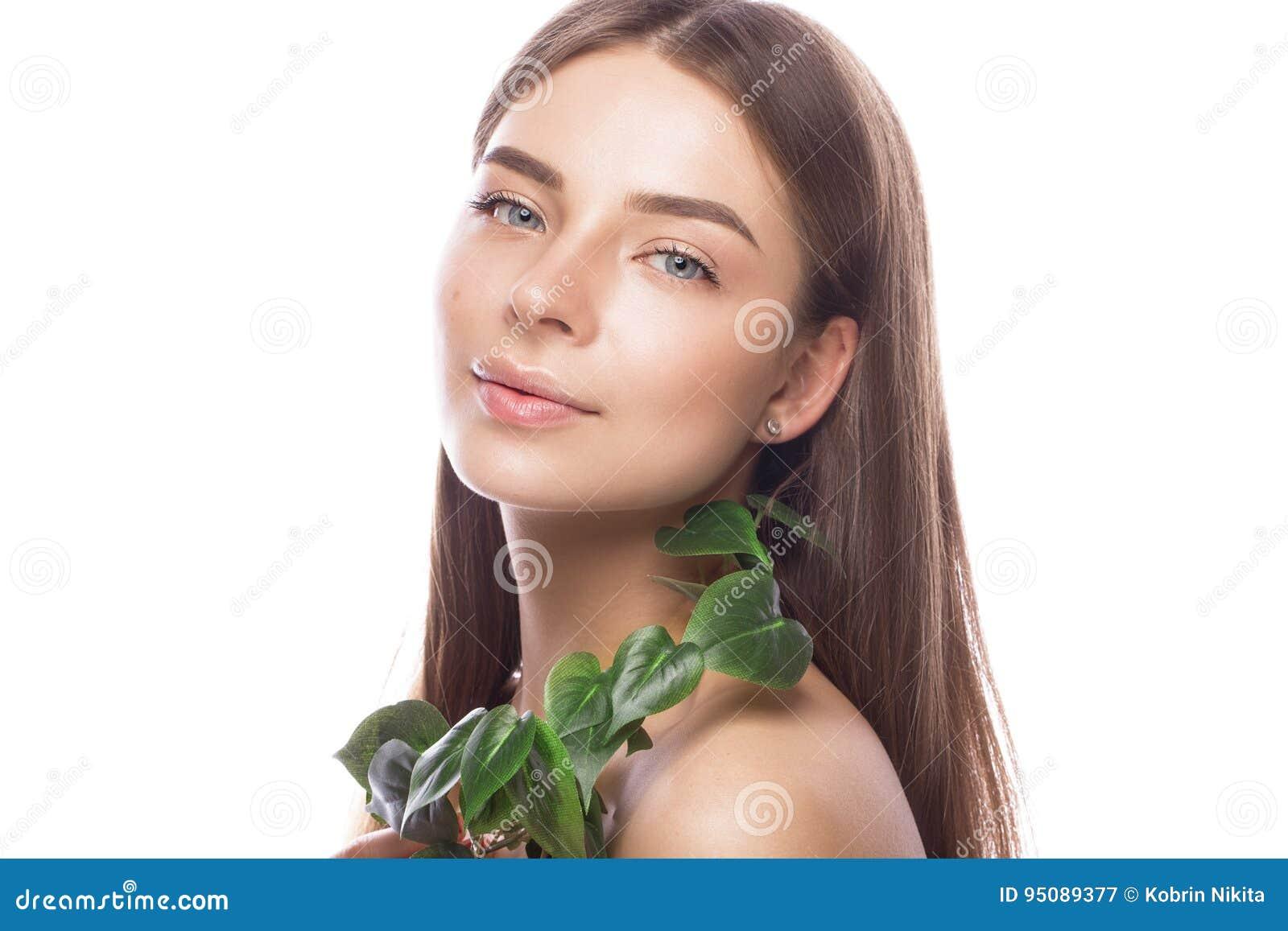 Mooi jong meisje met een lichte natuurlijke samenstelling en perfecte huid met Groene tak in haar hand Het Gezicht van de schoonh