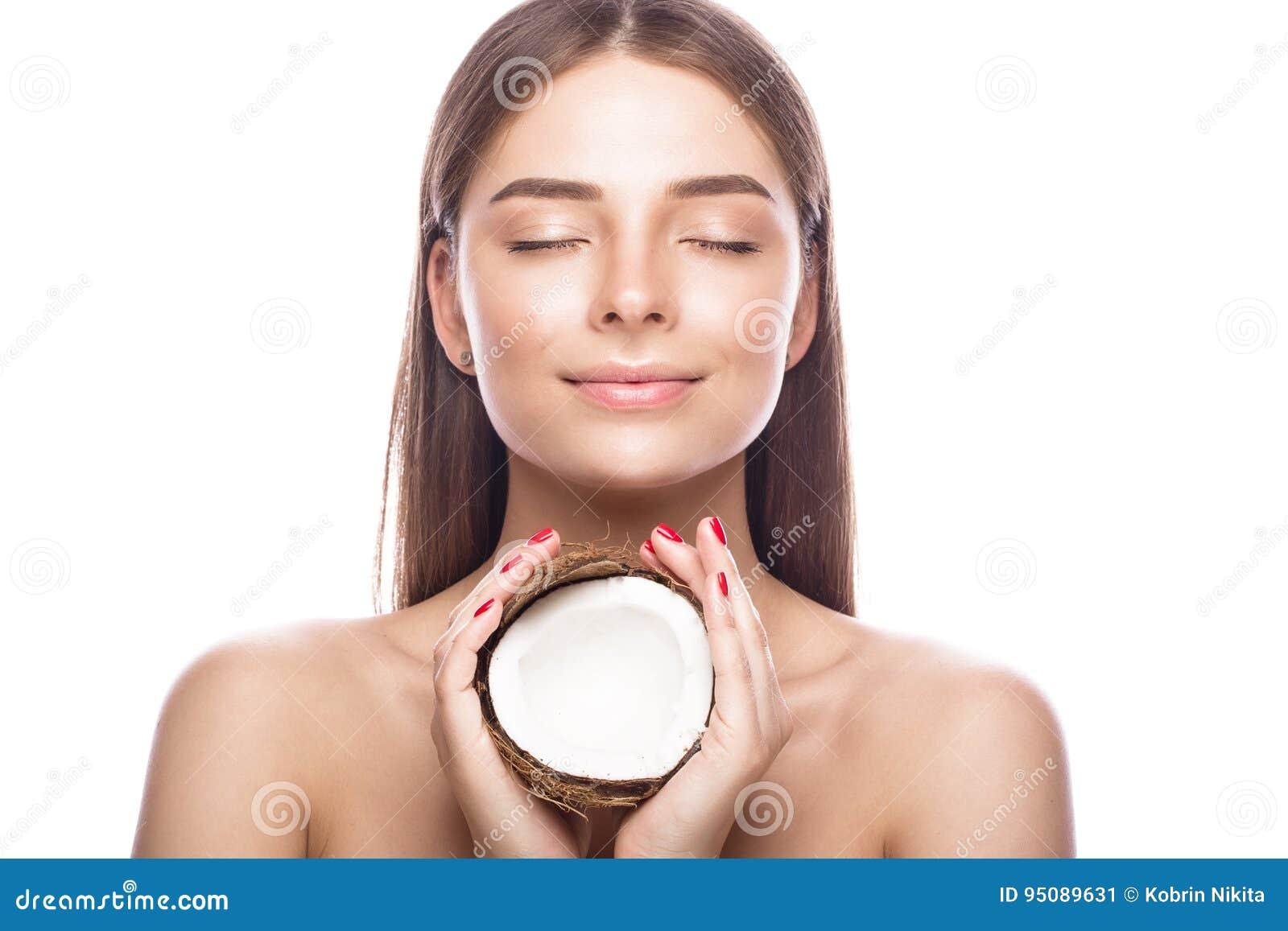 Mooi jong meisje met een lichte natuurlijke samenstelling en perfecte huid met kokosnoot in haar hand Het Gezicht van de schoonhe