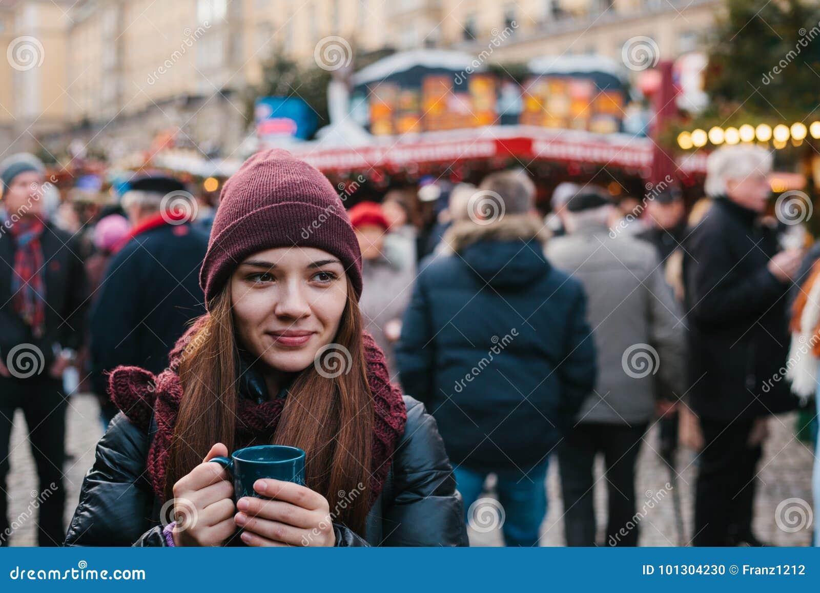 Mooi jong meisje met een mok van hete drank bij de Kerstmismarkt in Dresden Het vieren Kerstmis in Europa