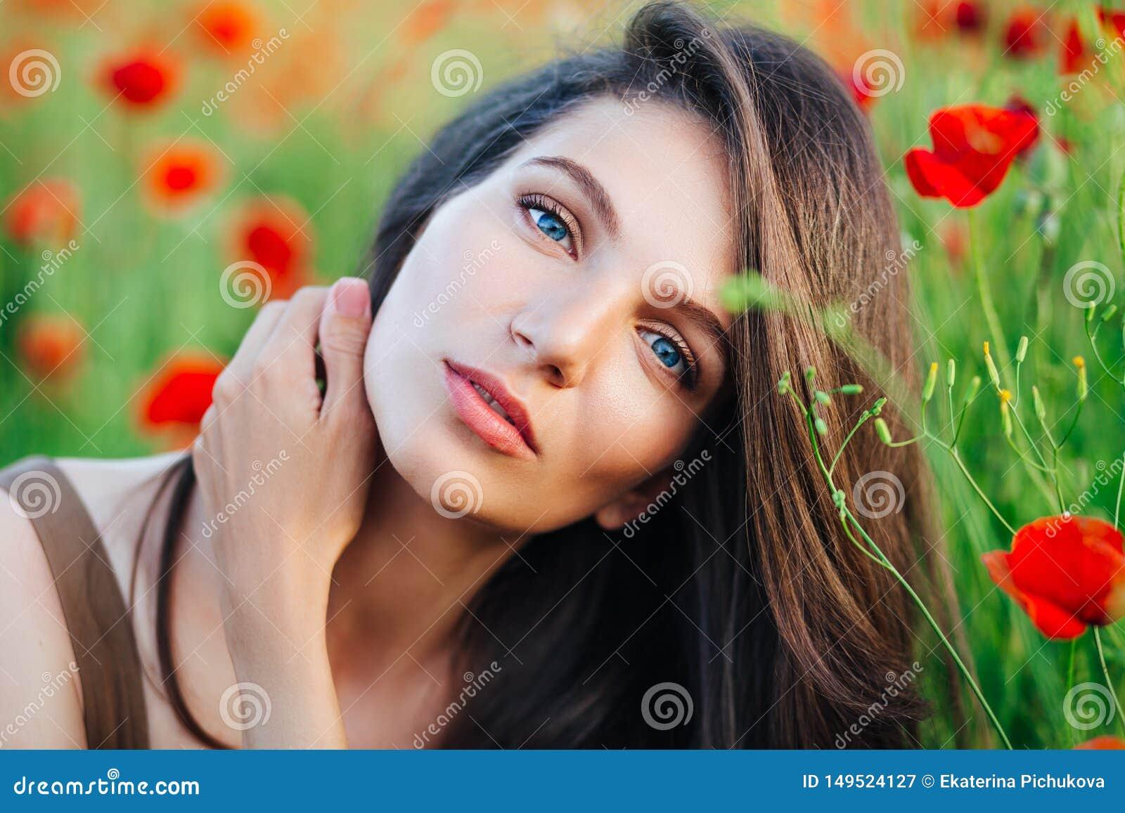 Mooi jong meisje op papavergebieden bij zonsondergang
