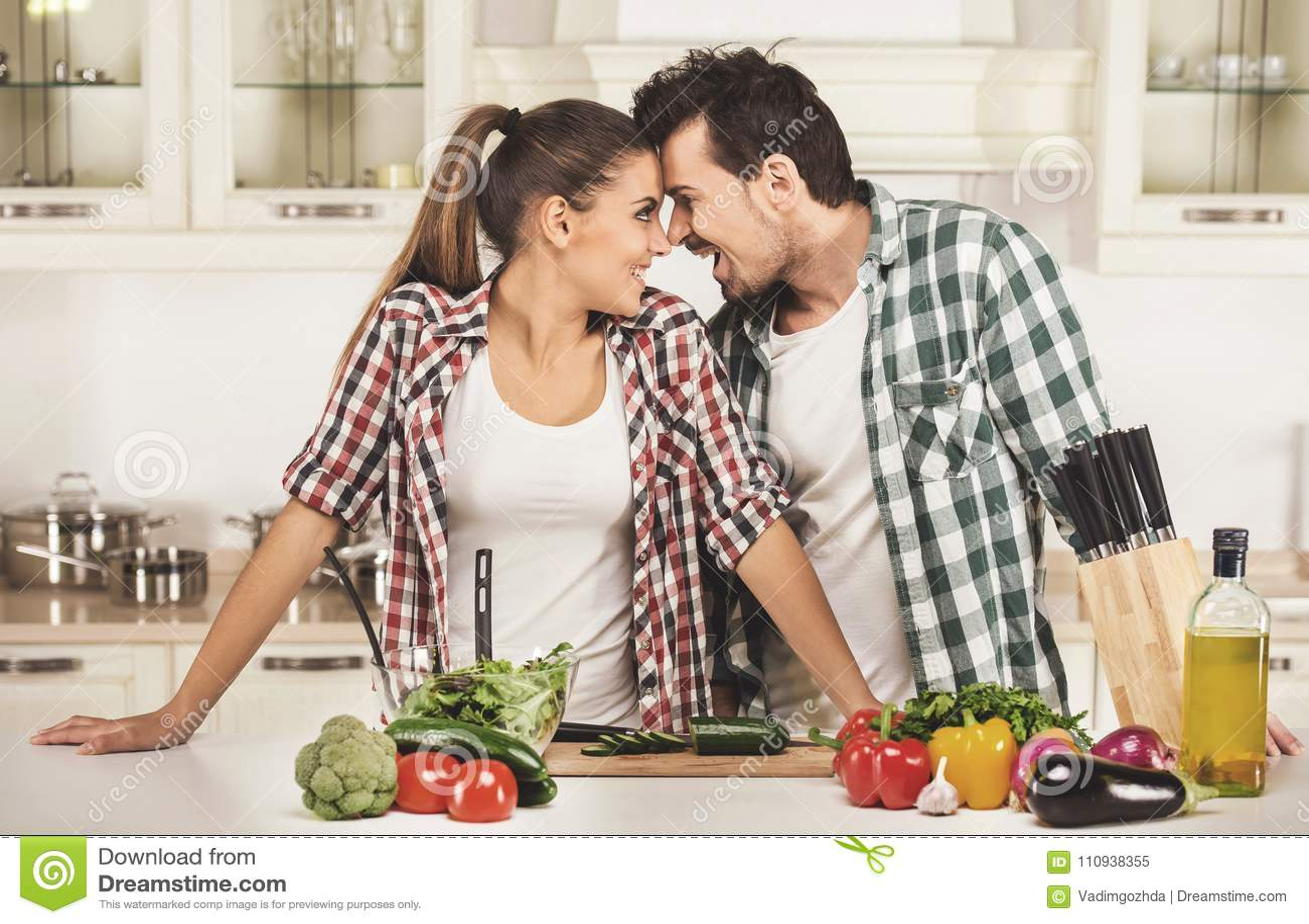 Mooi jong paar in de keuken terwijl het koken