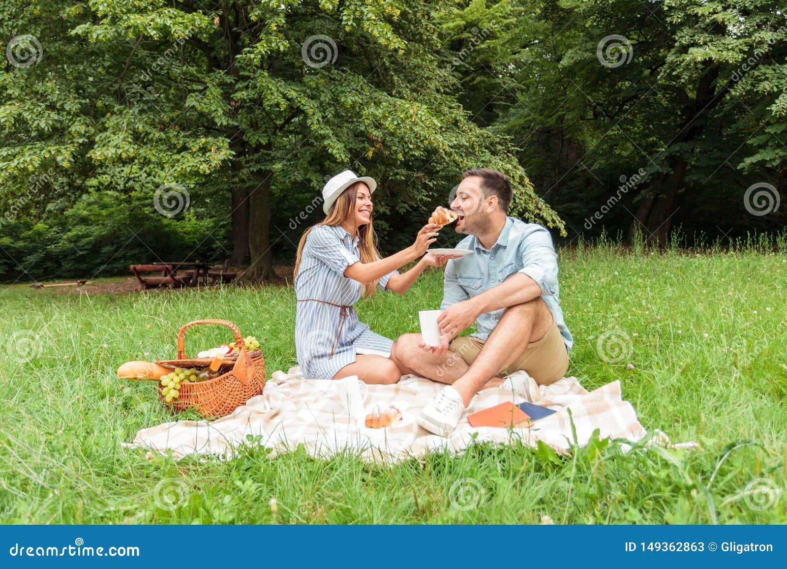Mooi jong paar die een ontspannende picknick in een park hebben