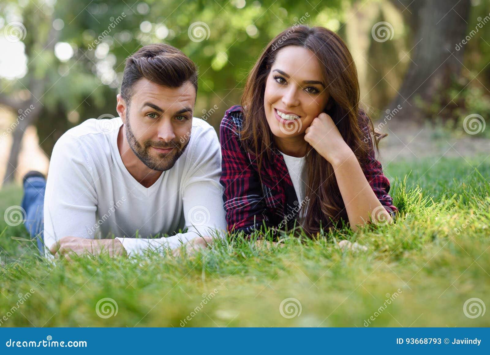 Mooi jong paar die op gras in een stedelijk park leggen